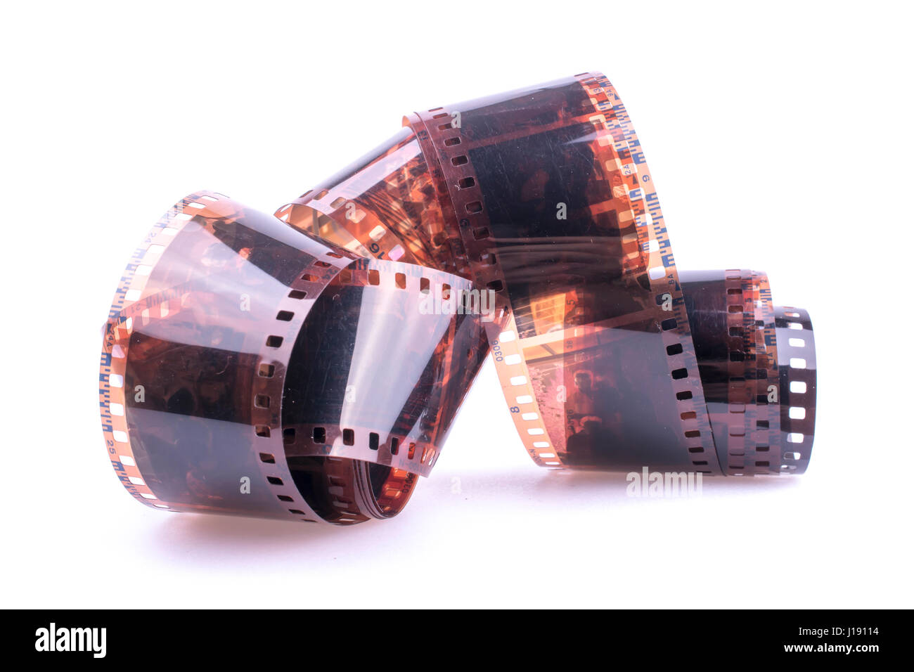 picture of curled color 35mm film against bright white background - Stock Image