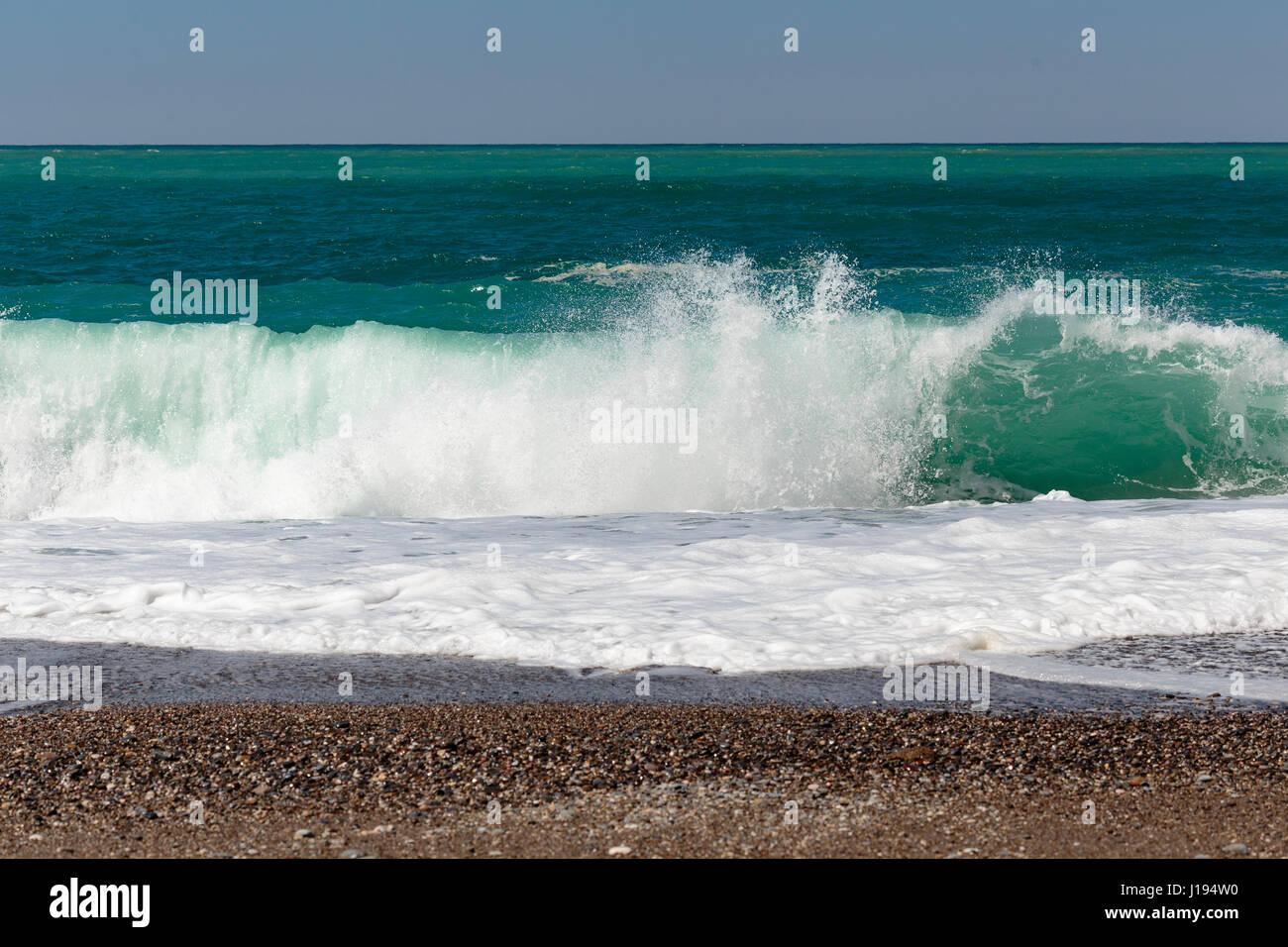 Dark blue sea with beautiful and powerful wave washing pebble beach - Stock Image