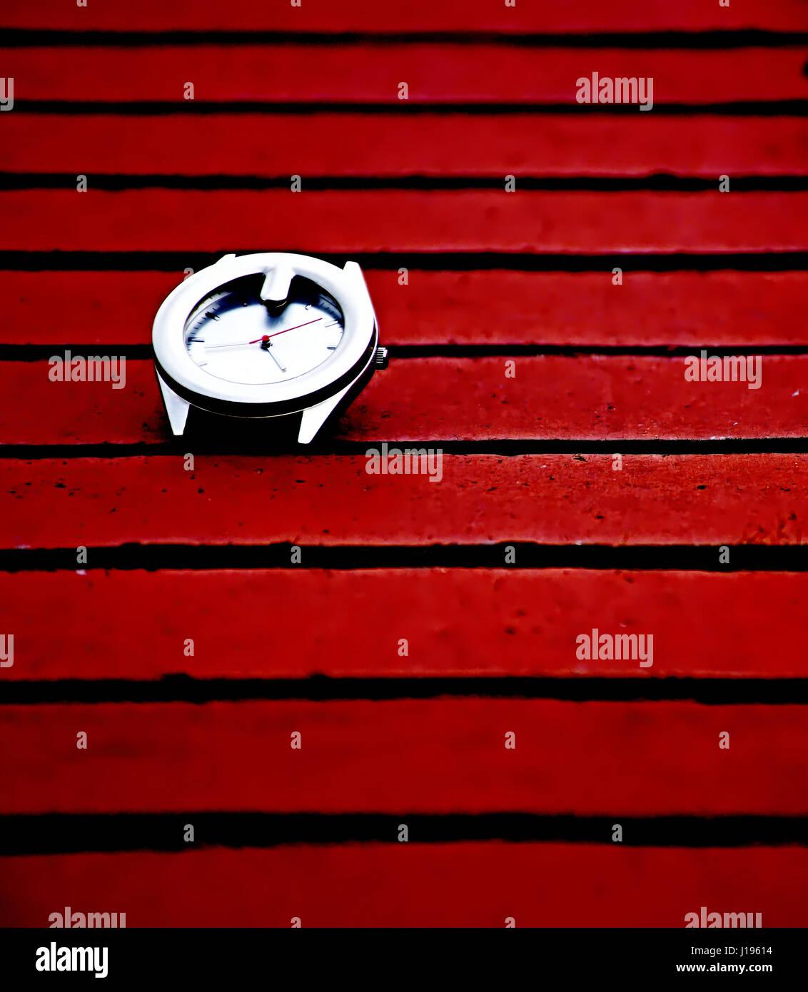 Watch on red bricks. - Stock Image