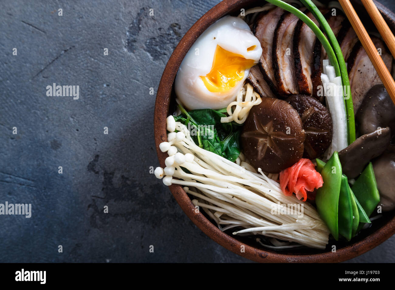 Duck noodles with egg and mushrooms in bowl on dark black stone texture background - Stock Image