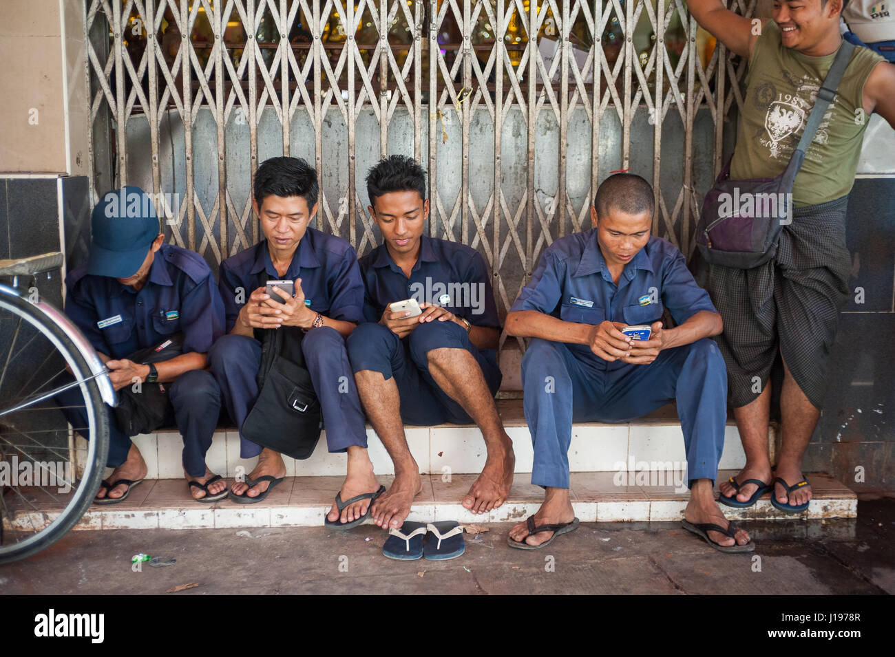 27.01.2017, Yangon, Republic of the Union of Myanmar, Asia - Workers sit in front of a Buddhist temple during their - Stock Image