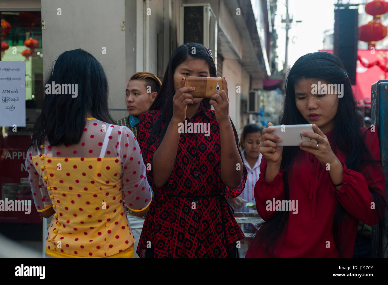 28.01.2017, Yangon, Myanmar, Asia - Young women look at their smartphones during Chinese New Year's celebrations. - Stock Image