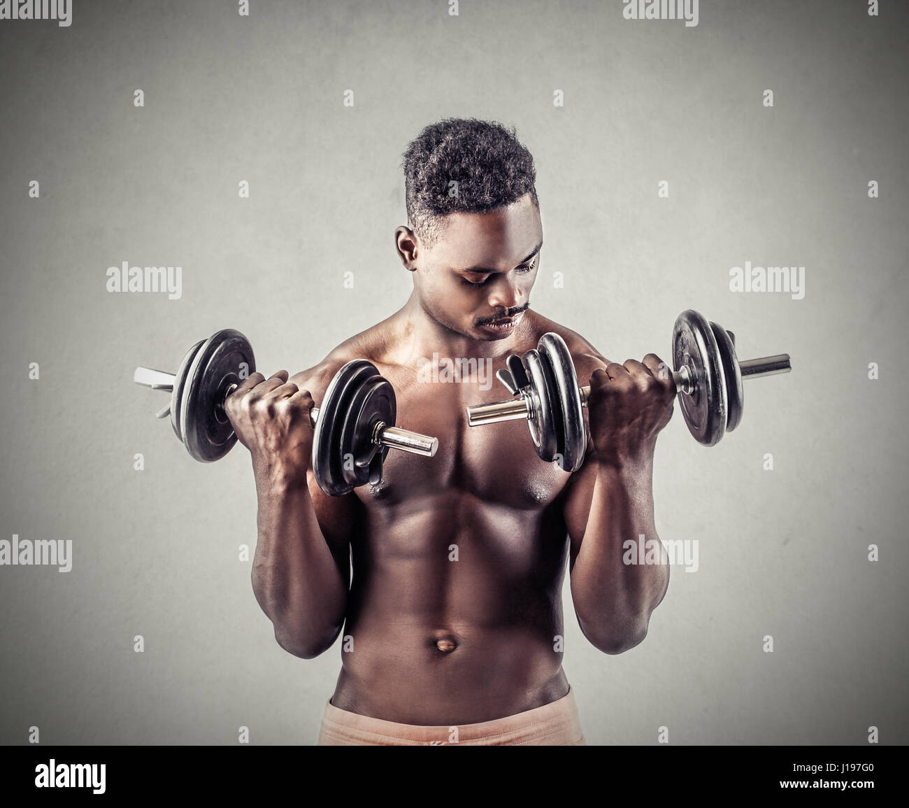 Black man working out with dumbbells - Stock Image