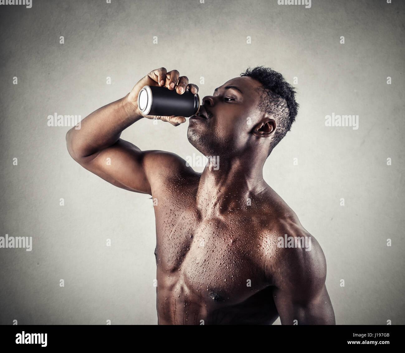 Shirtless black man drinking Stock Photo