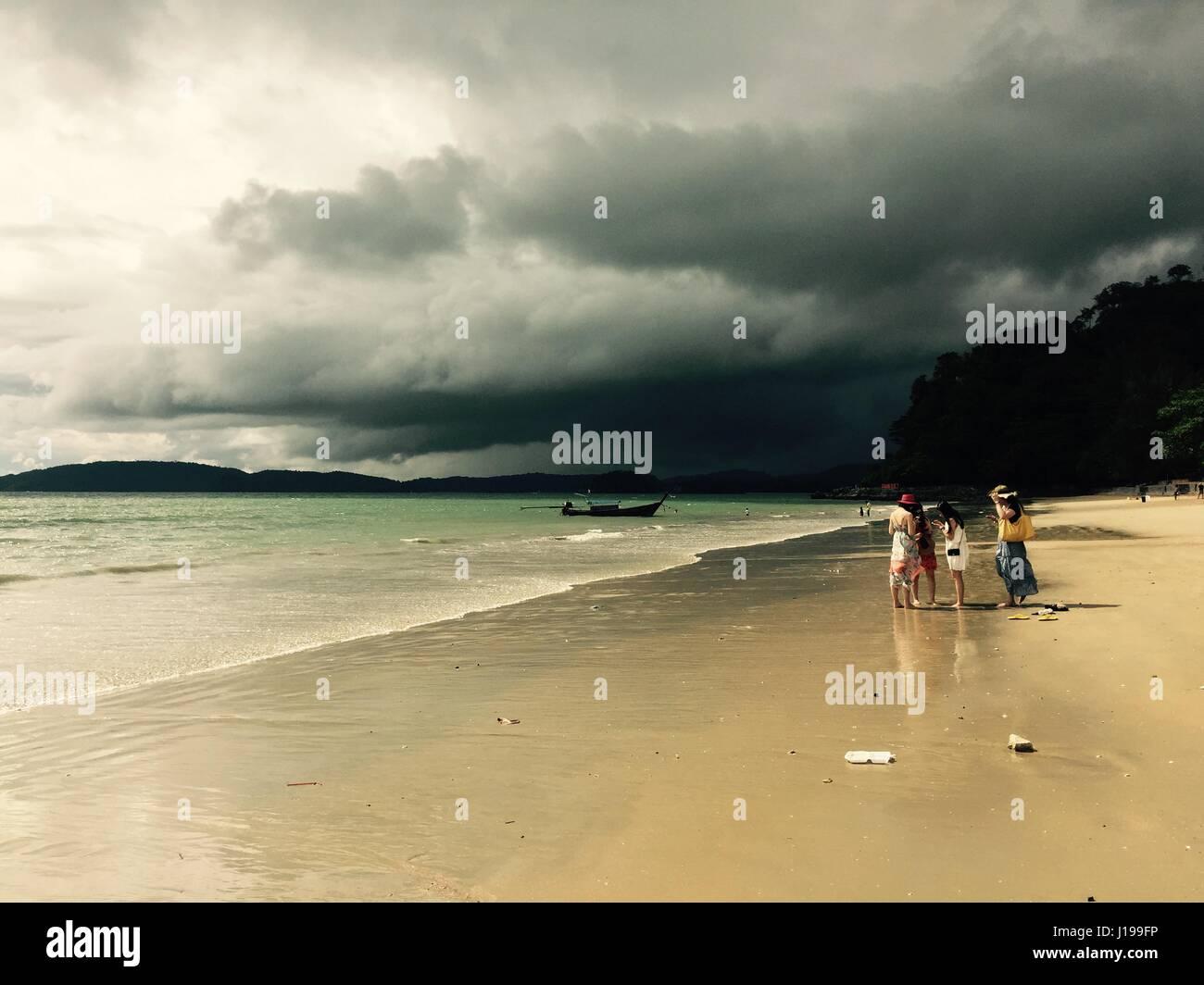 Ladies on a beach under dark skies in Krabi, Thailand. - Stock Image