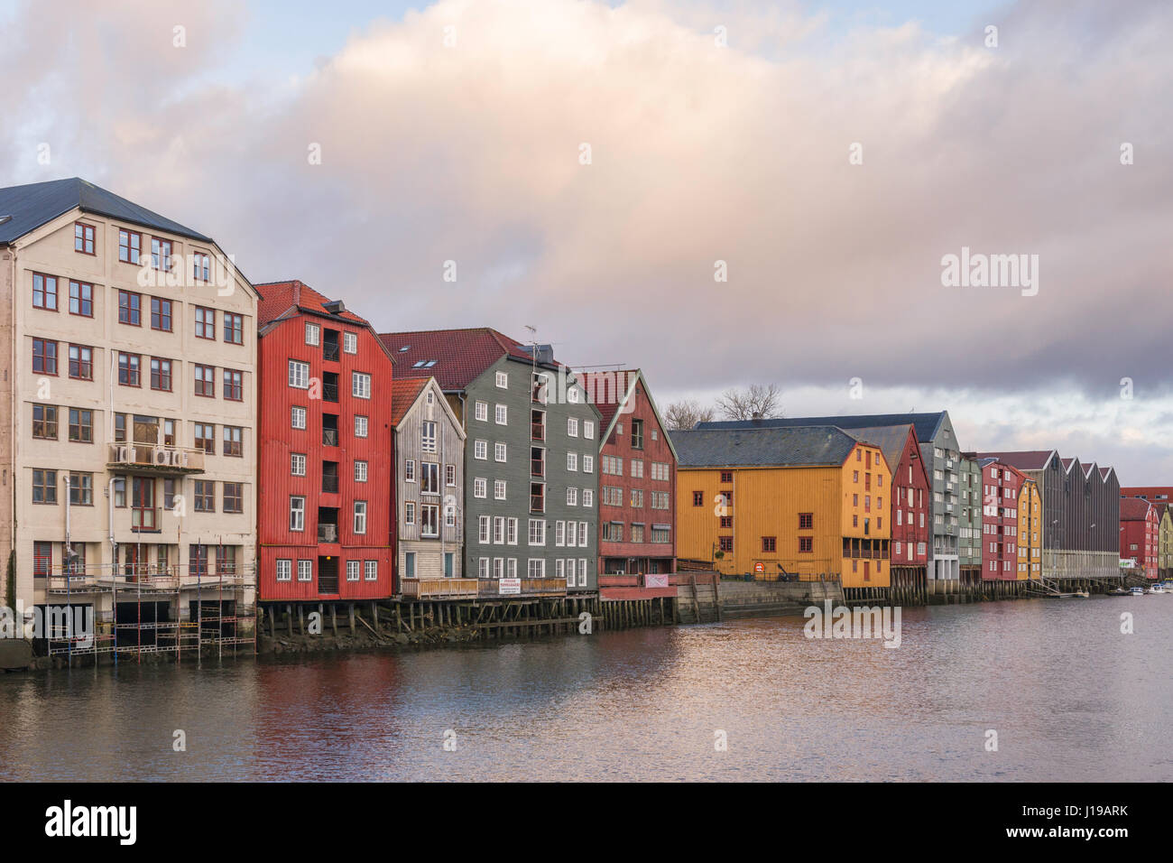 Traditional warehouses line the sides of the Nidelva River as it flows through Trondheim, Norway. - Stock Image