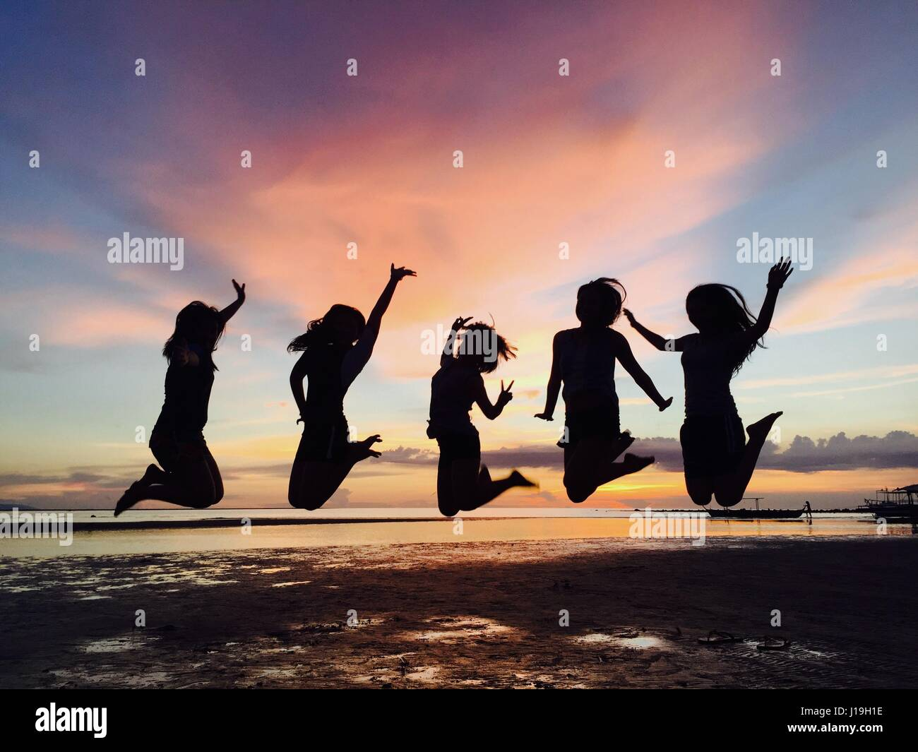 Aim High. Girl power jump shot take at sunset - Stock Image