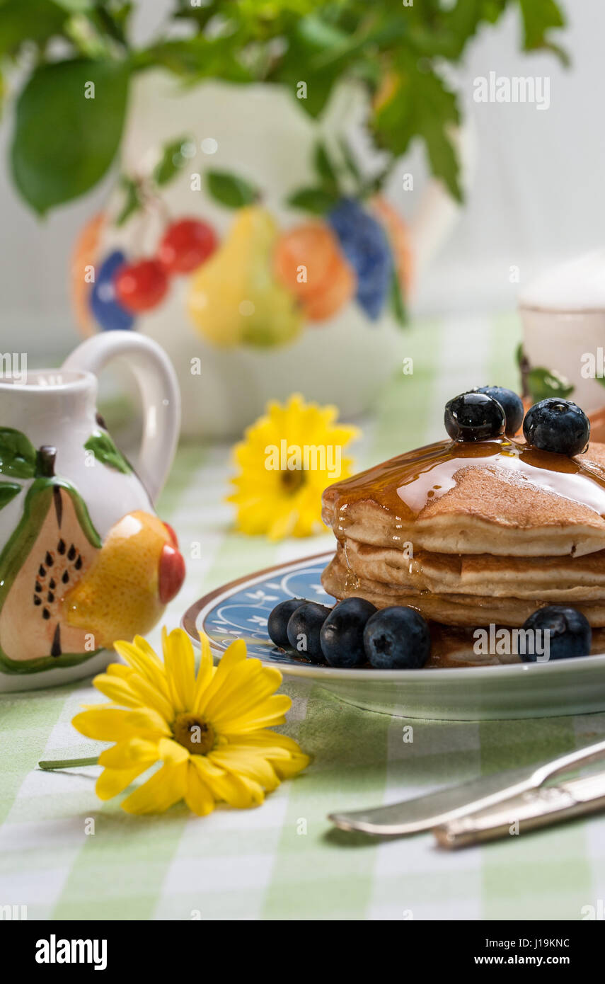 Breakfast scenery: tasty pancakes with blueberries with colourful fruit theme tea set. - Stock Image
