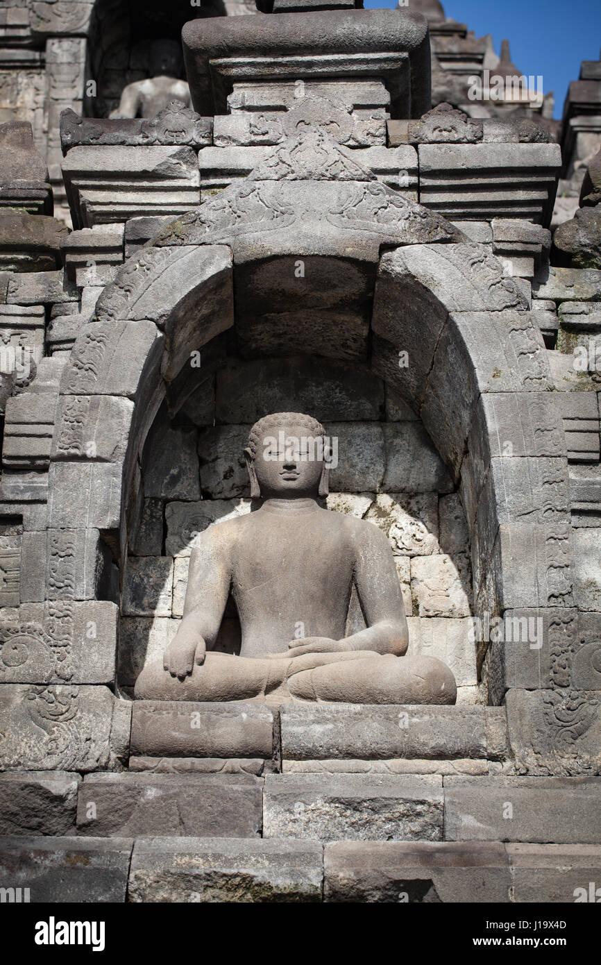 A meditating Buddha statue at the Borobudur in Indonesia, Asia. - Stock Image