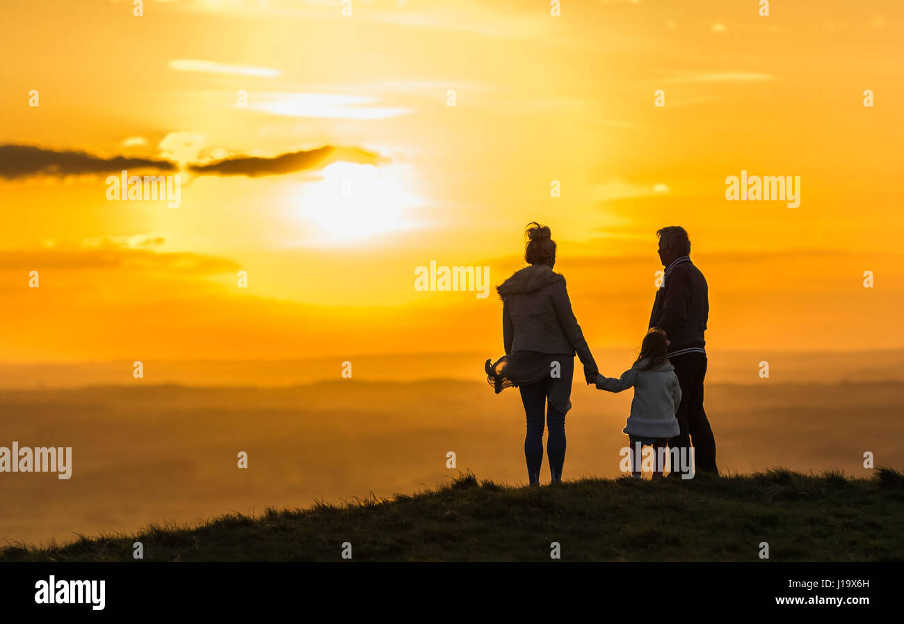 Love concept. Family love and togetherness. Small family standing on a hill watching the sunset while holding hands. - Stock Image