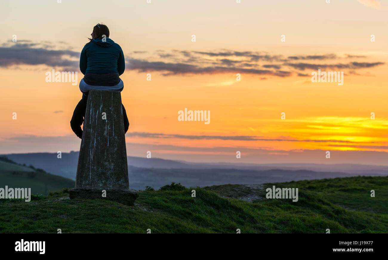 Couple at a monument on top of a hill overlooking the countryside at sunset, on the south downs hills, in the south - Stock Image