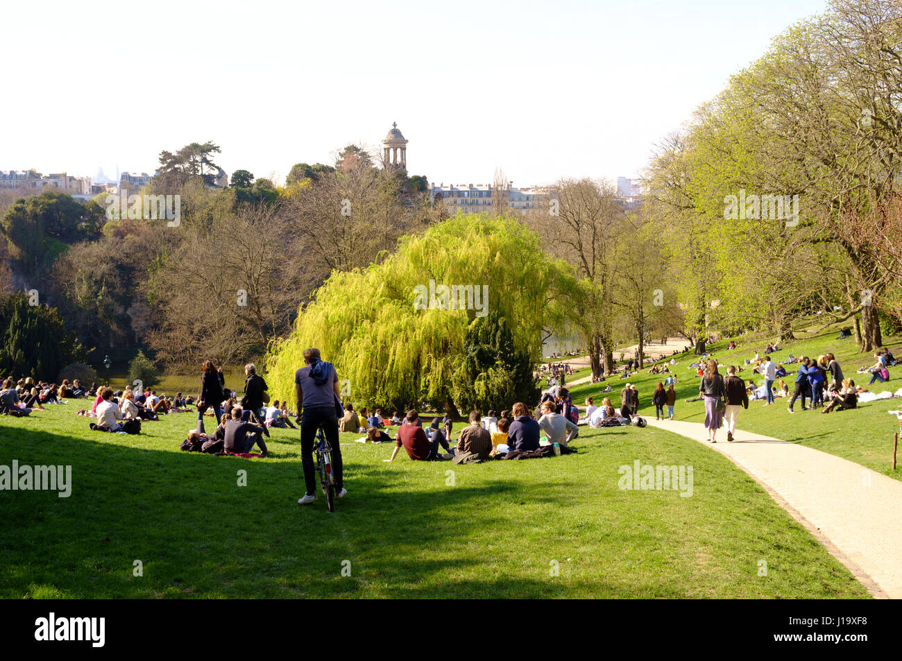 People enjoying the spring sun in the Buttes-Chaumont Park, Paris, France - Stock Image