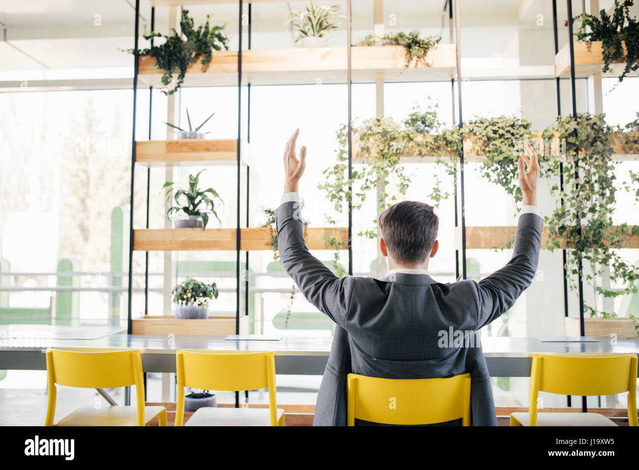 Successful business man happy smile hold fist gesture view from back, handsome young businessman with raised hands Stock Photo