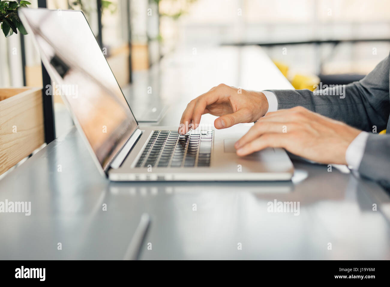 Photo businessman working on modern loft office. Man sitting wood table and using contemporary notebook, texting - Stock Image