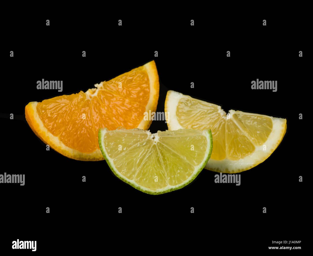 Orange Lime and Lemon Segments Against a Black Background - Stock Image