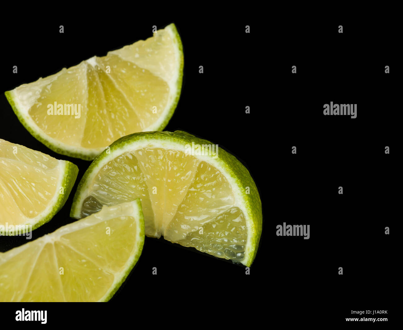 Fresh Ripe Juicy Lime Segments Against a Black Background - Stock Image