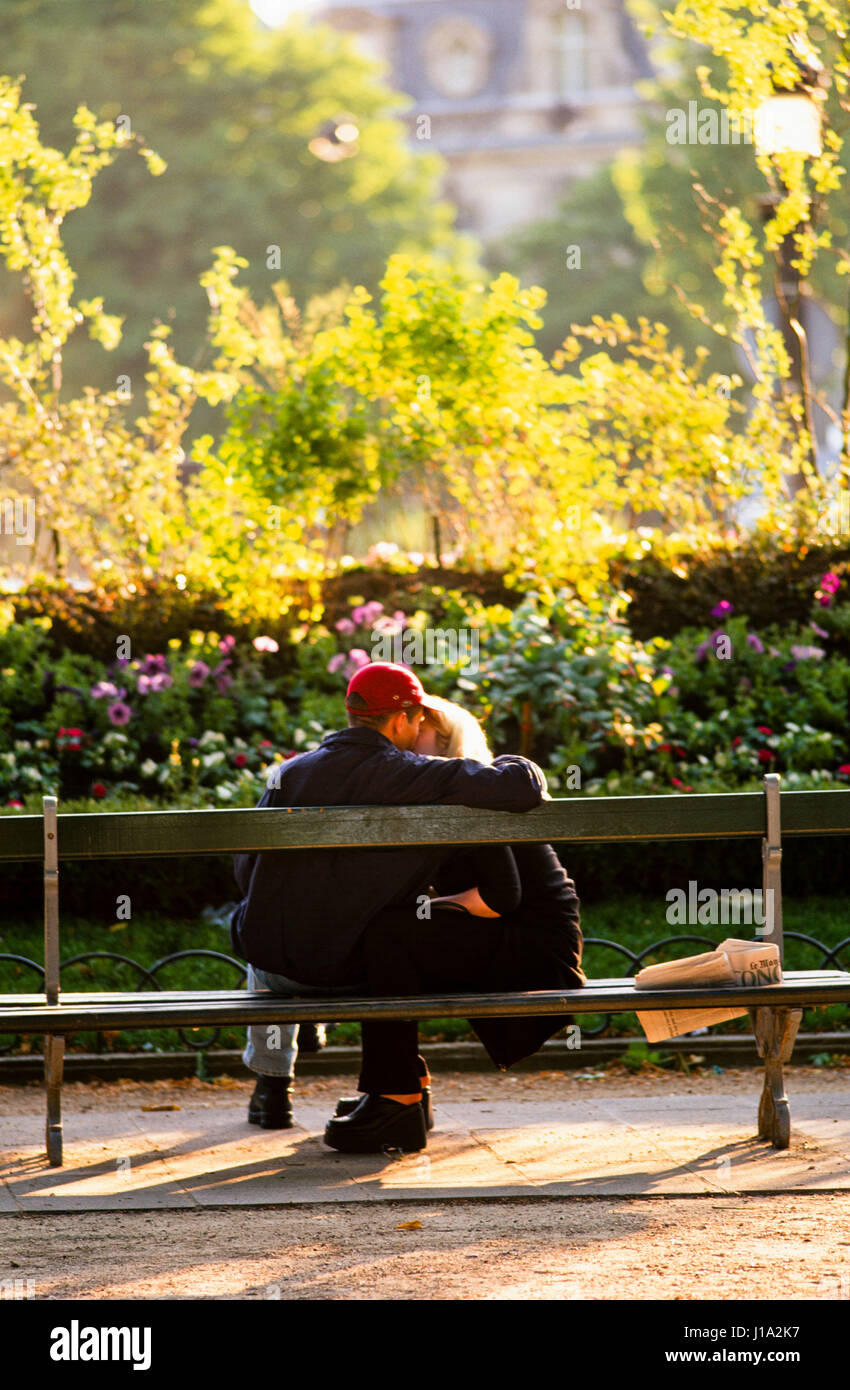 Couple kissing on park bench. - Stock Image