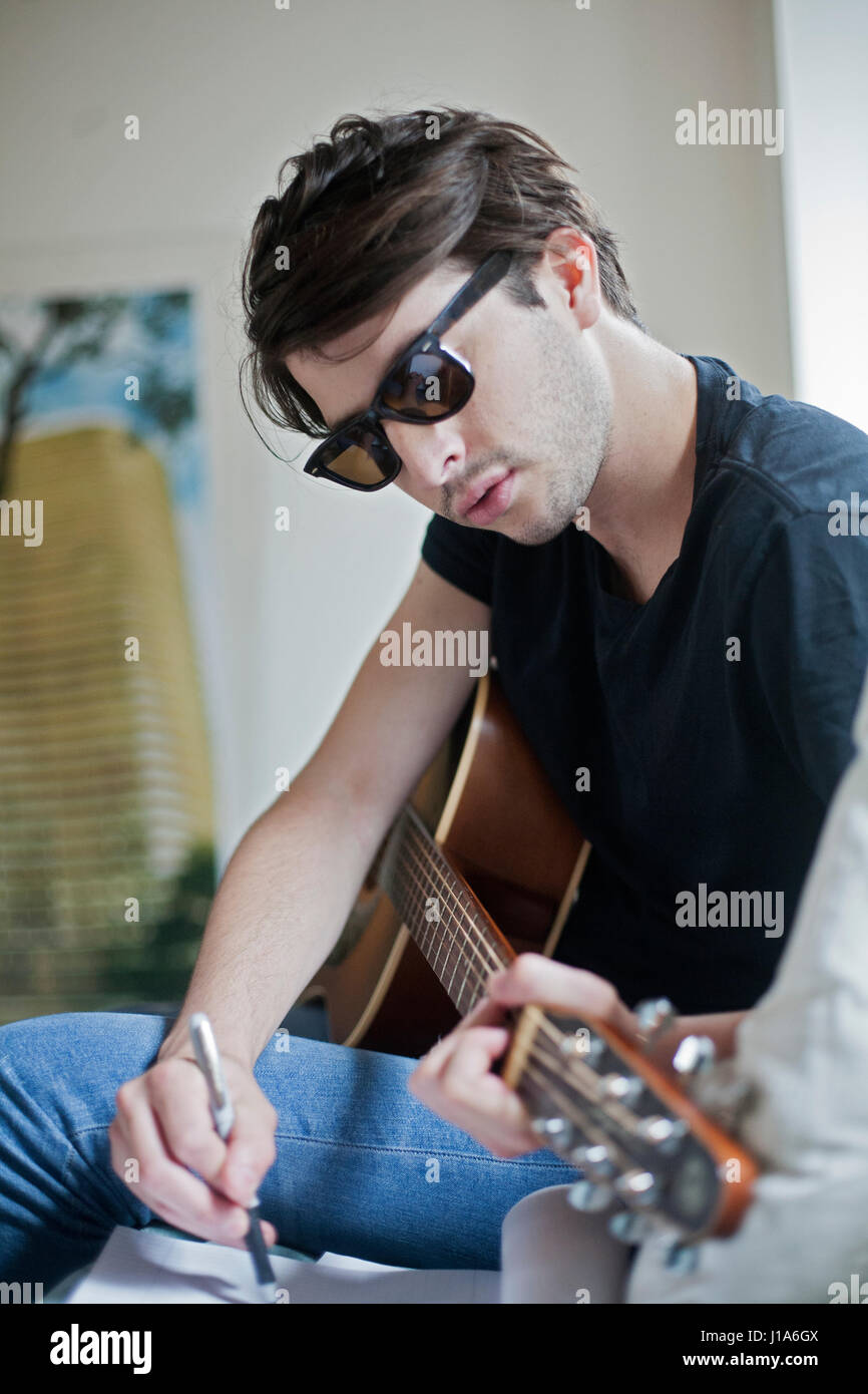 Young musician writing songs on an acoustic guitar - Stock Image