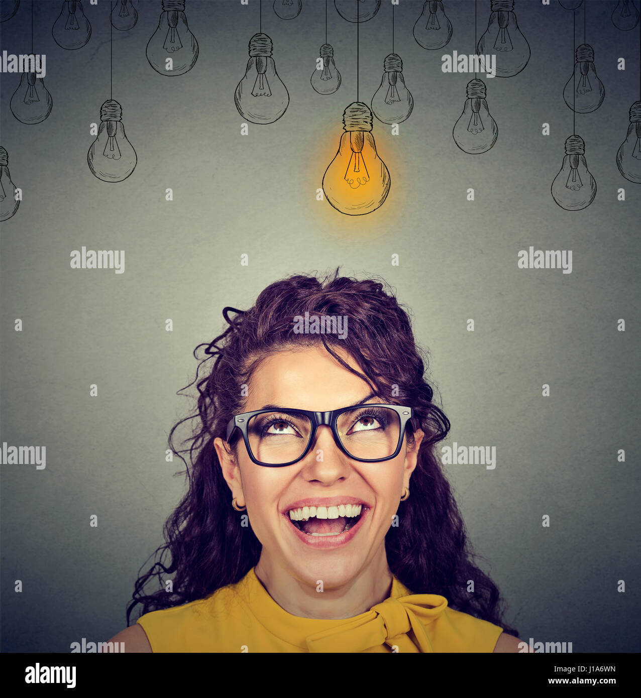 Portrait happy beautiful woman in glasses looking up at idea light bulb above head isolated on gray wall background - Stock Image