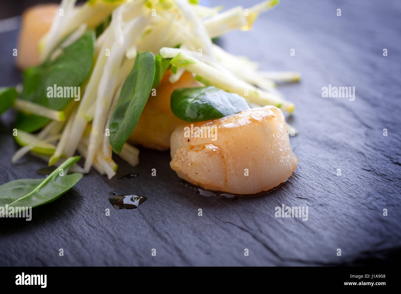 Scallop salad with apple, spinach on a stone plate. - Stock Image