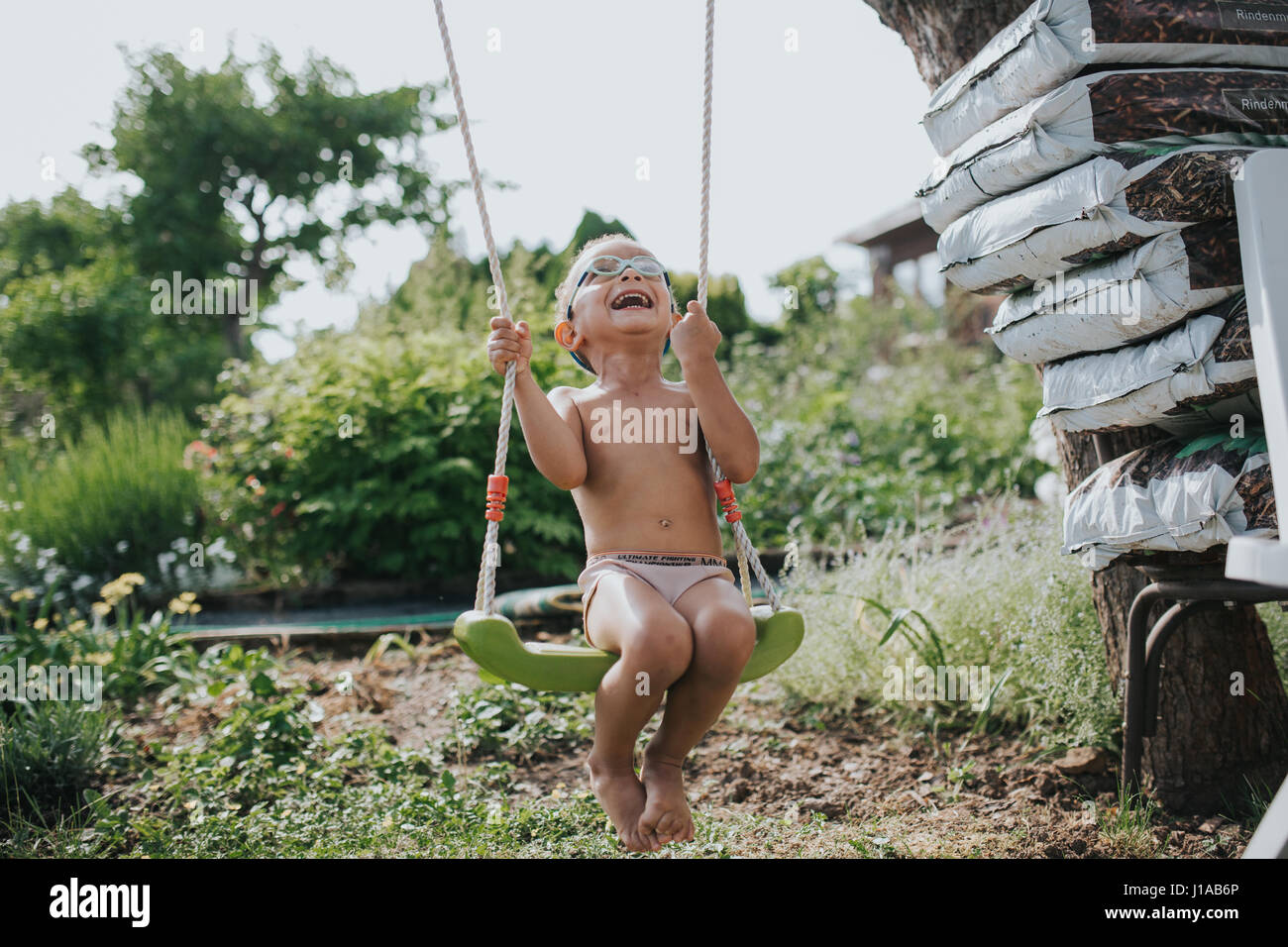 young coloured boy is having fun on the swing Stock Photo