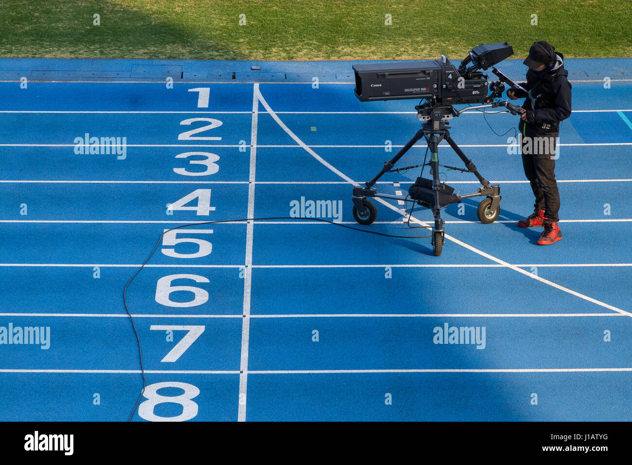 A TV camera and cameraman on a running track in a stadium in Komazawa Olympic Park, Tokyo, Japan. Monday January - Stock Image