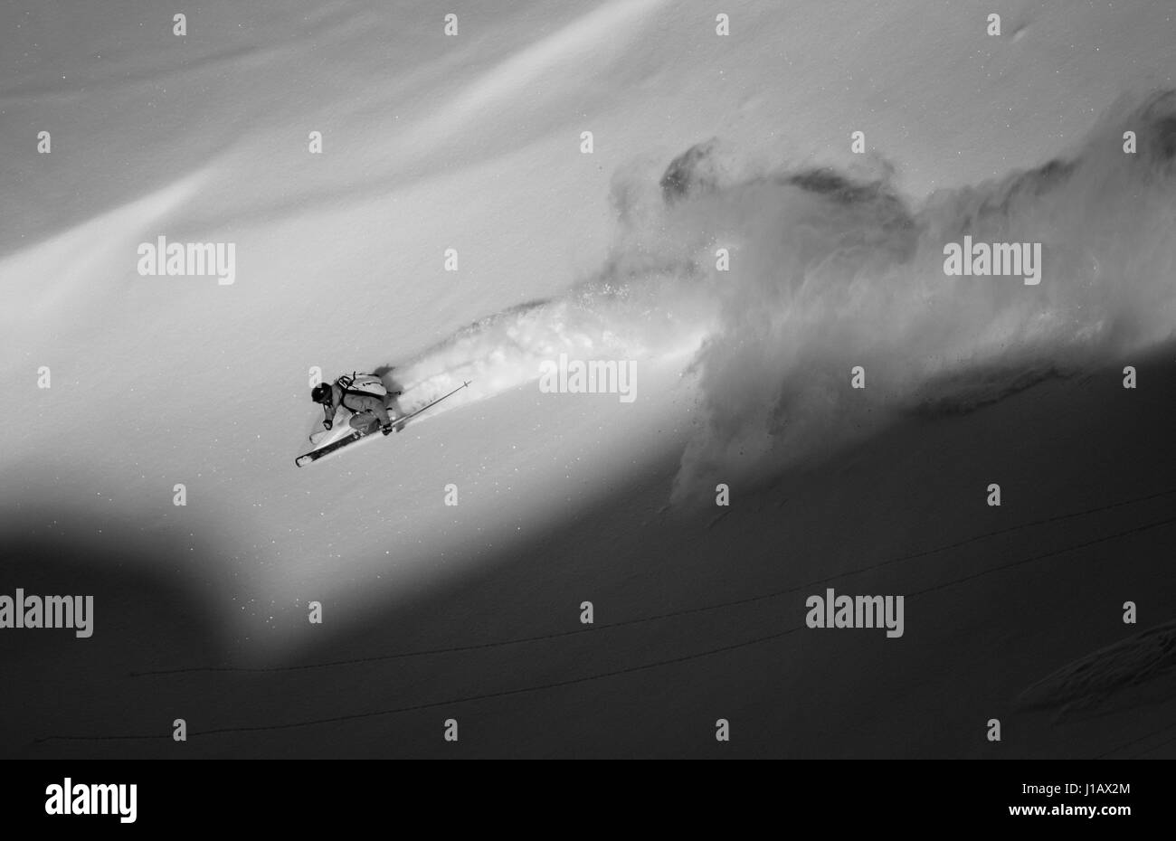 A skier races down off-piste and sprays snow behind him at a mountain in the Gastein Valley, Austria. - Stock Image