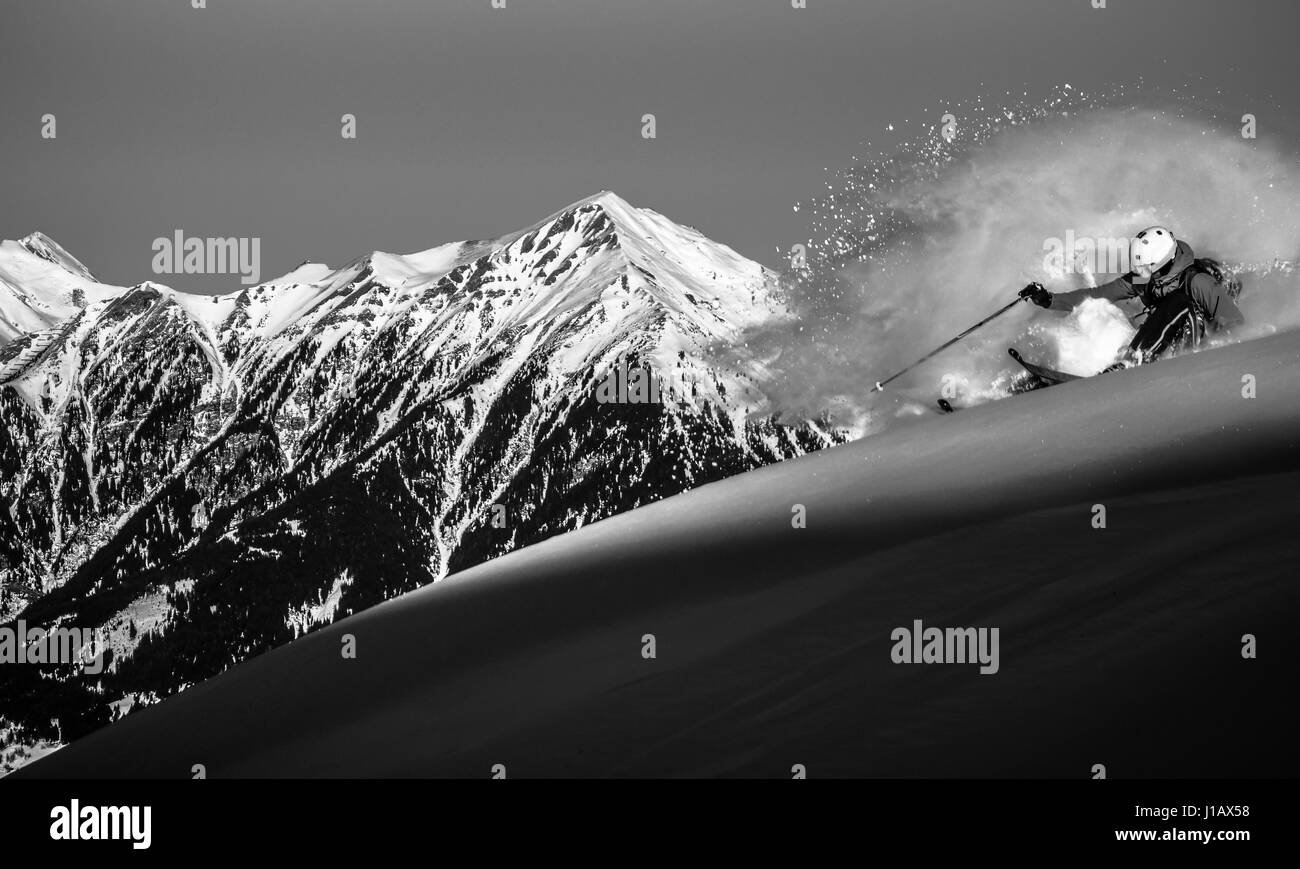 A skier races down off-piste at a snowy mountain in the Gastein Valley, Austria. - Stock Image