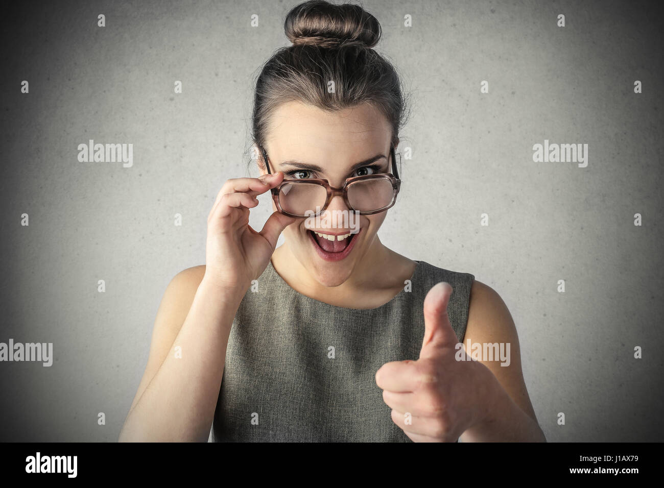 Brunette woman showing like sign - Stock Image