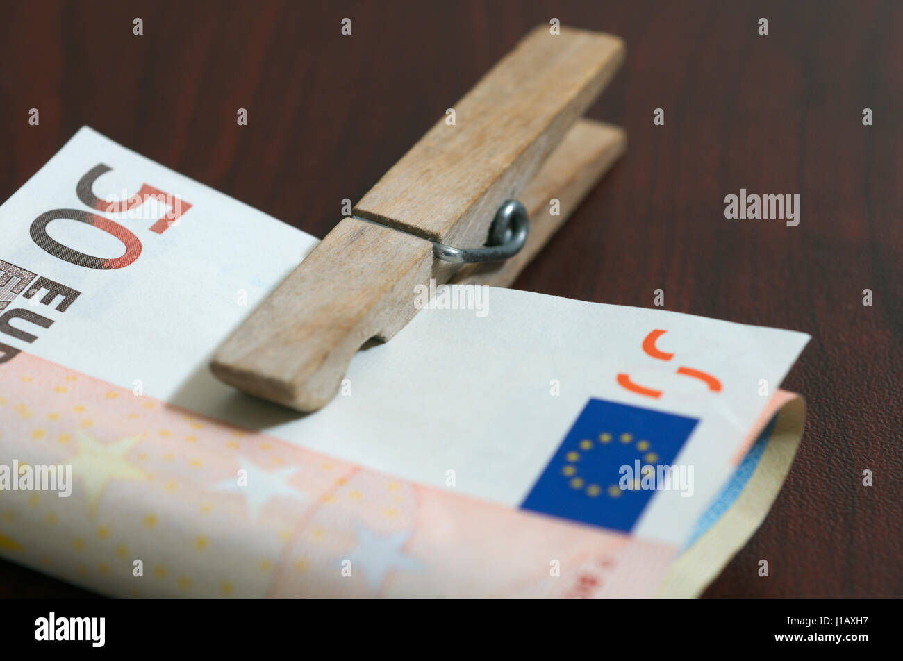 Euro banknotes held with a clothes peg - Stock Image