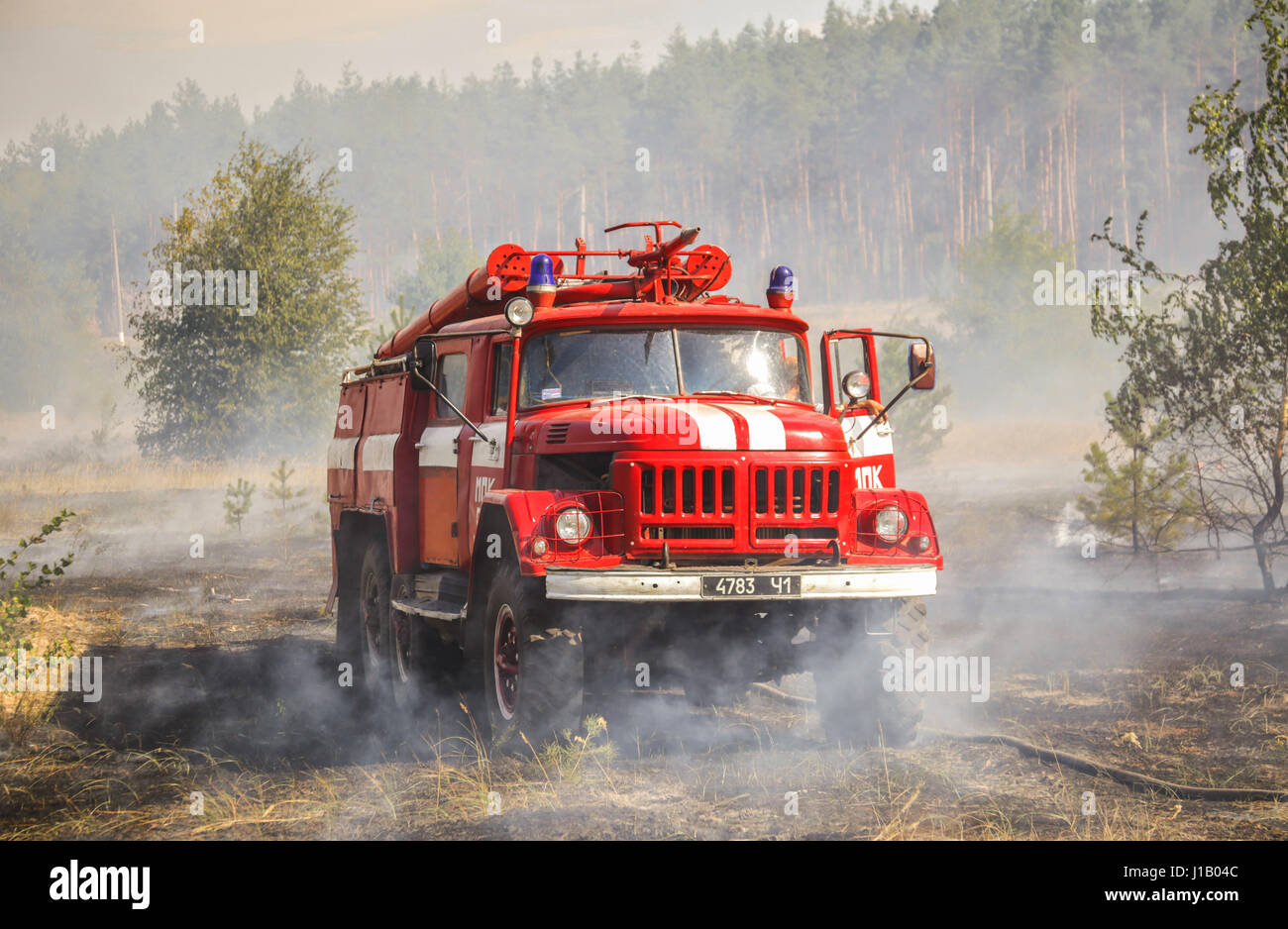 Forest fire due to dry weather in summer, Donbass , Ukraine. A typical USSR firetrack ZIL-131 is on photo. - Stock Image