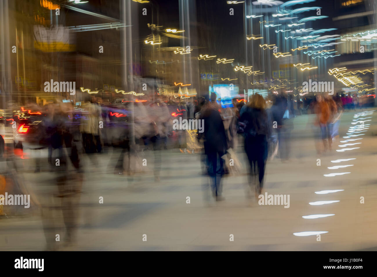 Abstract vintage tone motion. Blurred image of Street, two girls walking along sidewalk, bright city lights with - Stock Image