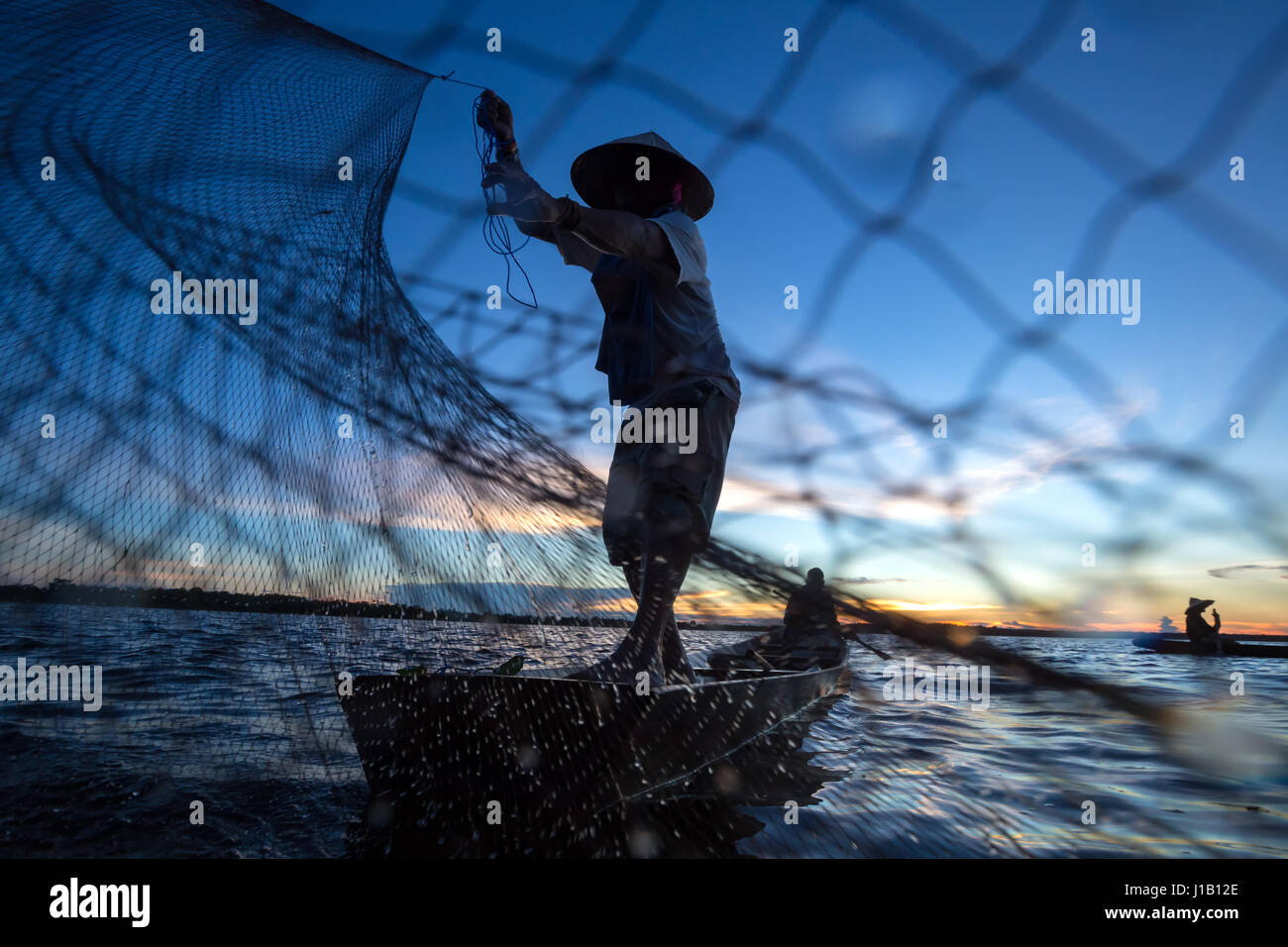 Thai fisherman on wooden boat casting a net for catching freshwater fish in nature river in the early evening before - Stock Image