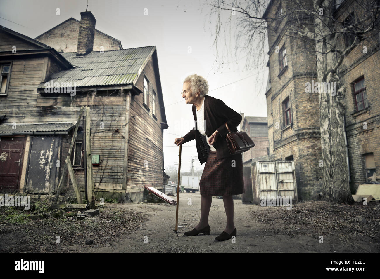 Old lady walking with stick in empty village - Stock Image