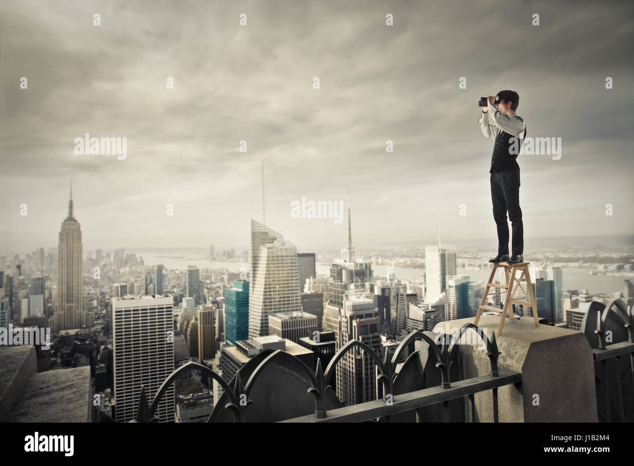 Businessman with telescope looking at the city - Stock Image