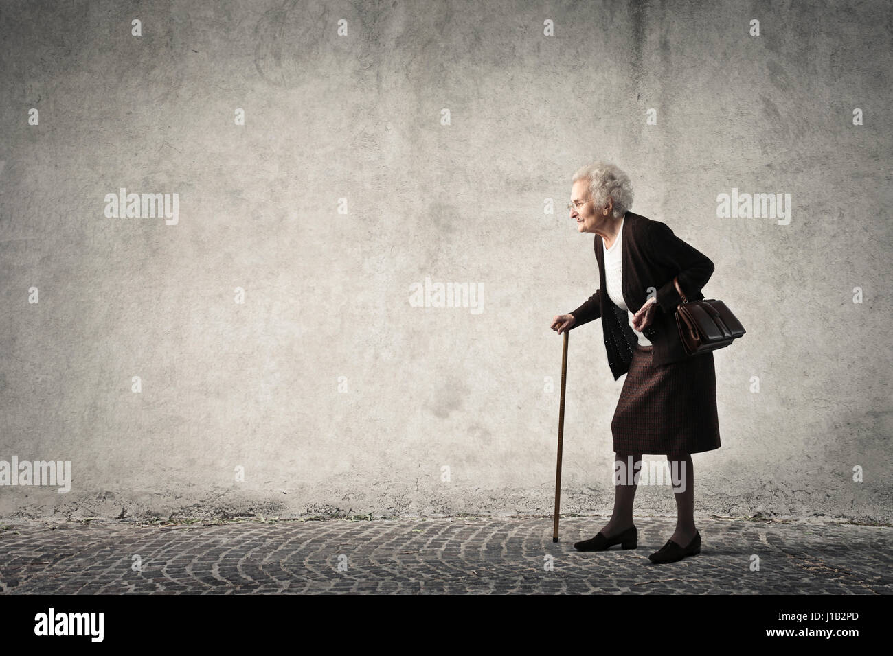 Old lady walking with stick in front of grey wall - Stock Image