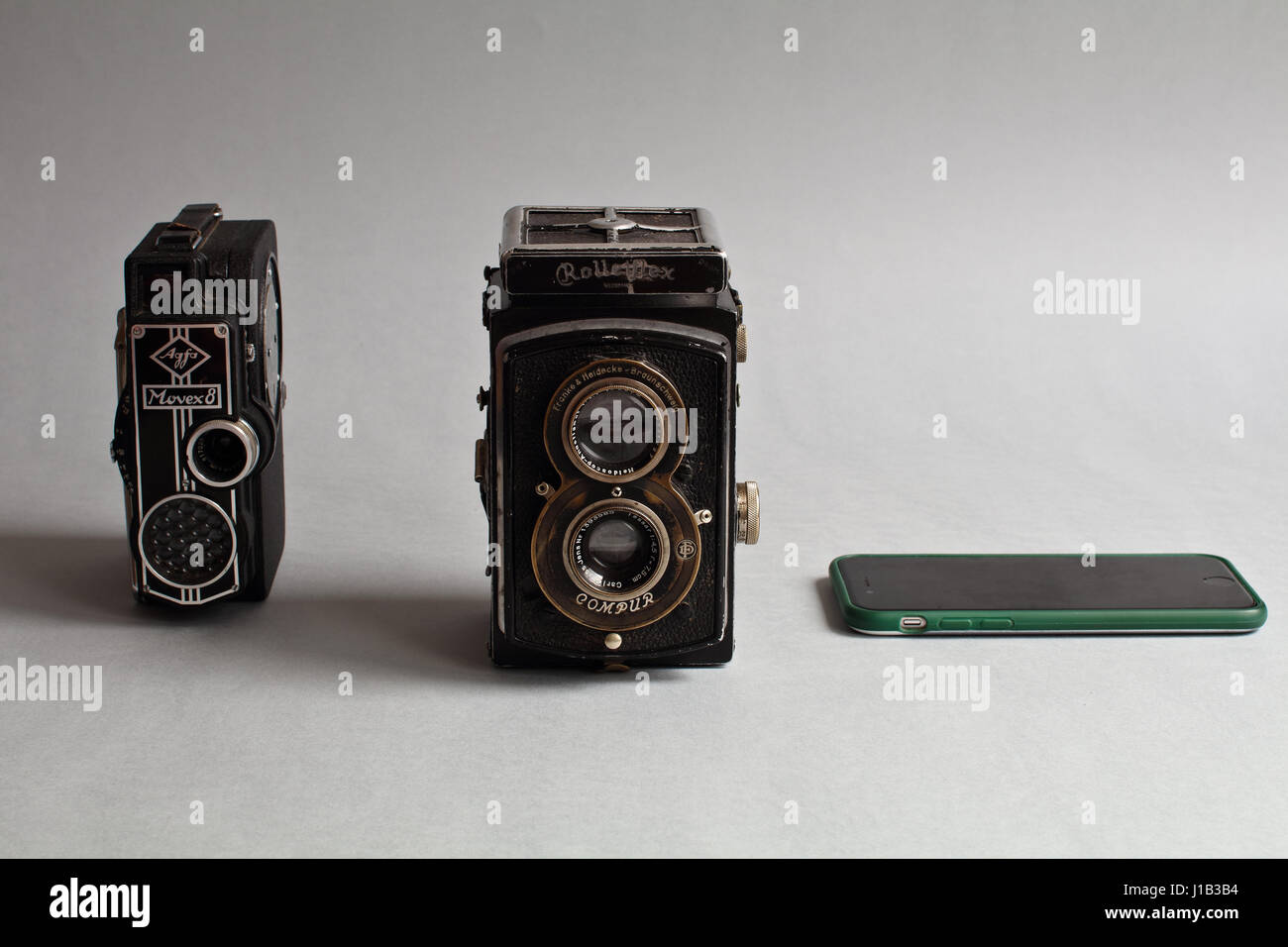 More than two in one. Smartphone is more than cameras. Antique analog camera. Optical and mechanical instruments - Stock Image