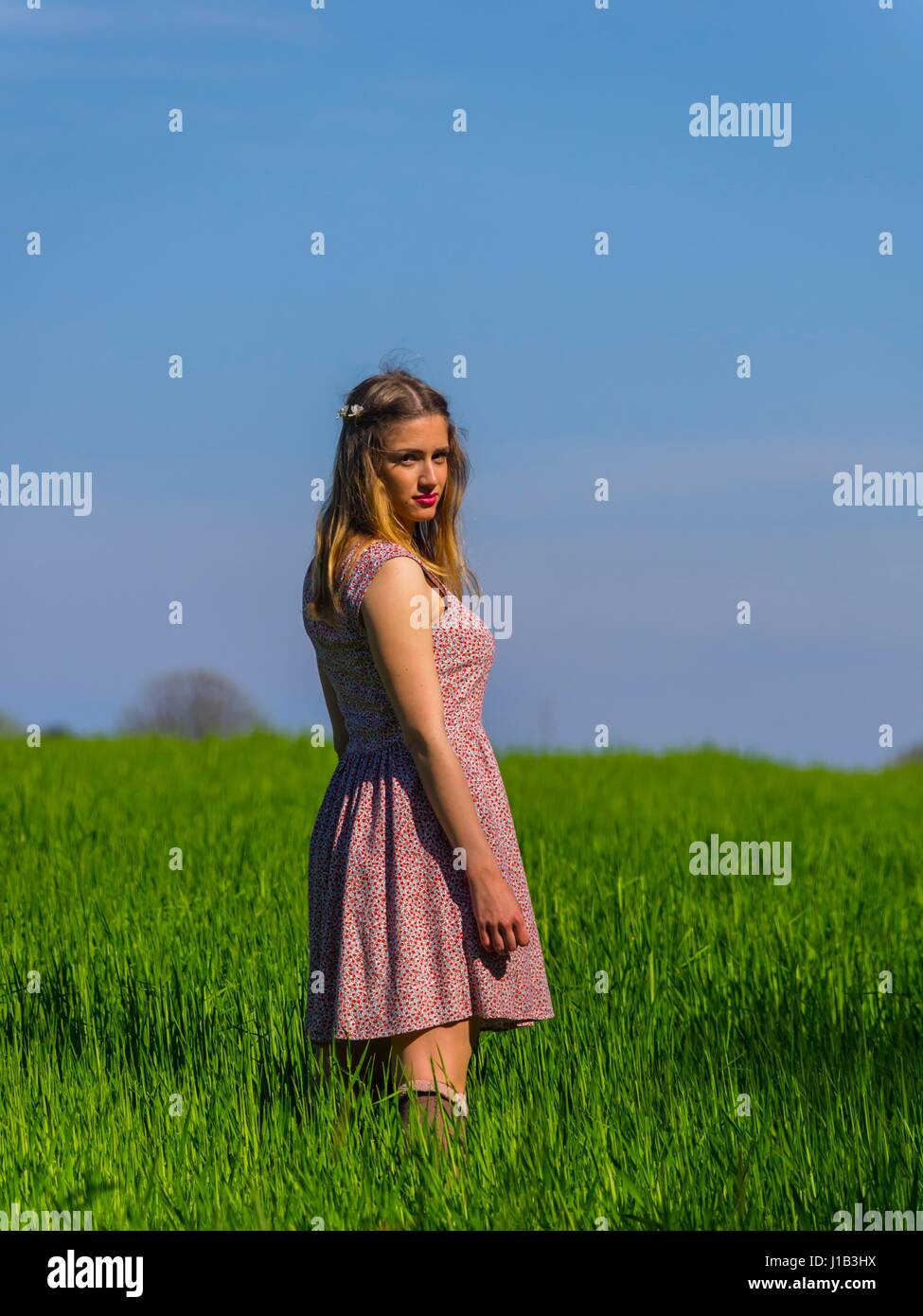 Country-girl in green-field side-view three-quarter length looking at camera eyes-contact farm girl - Stock Image