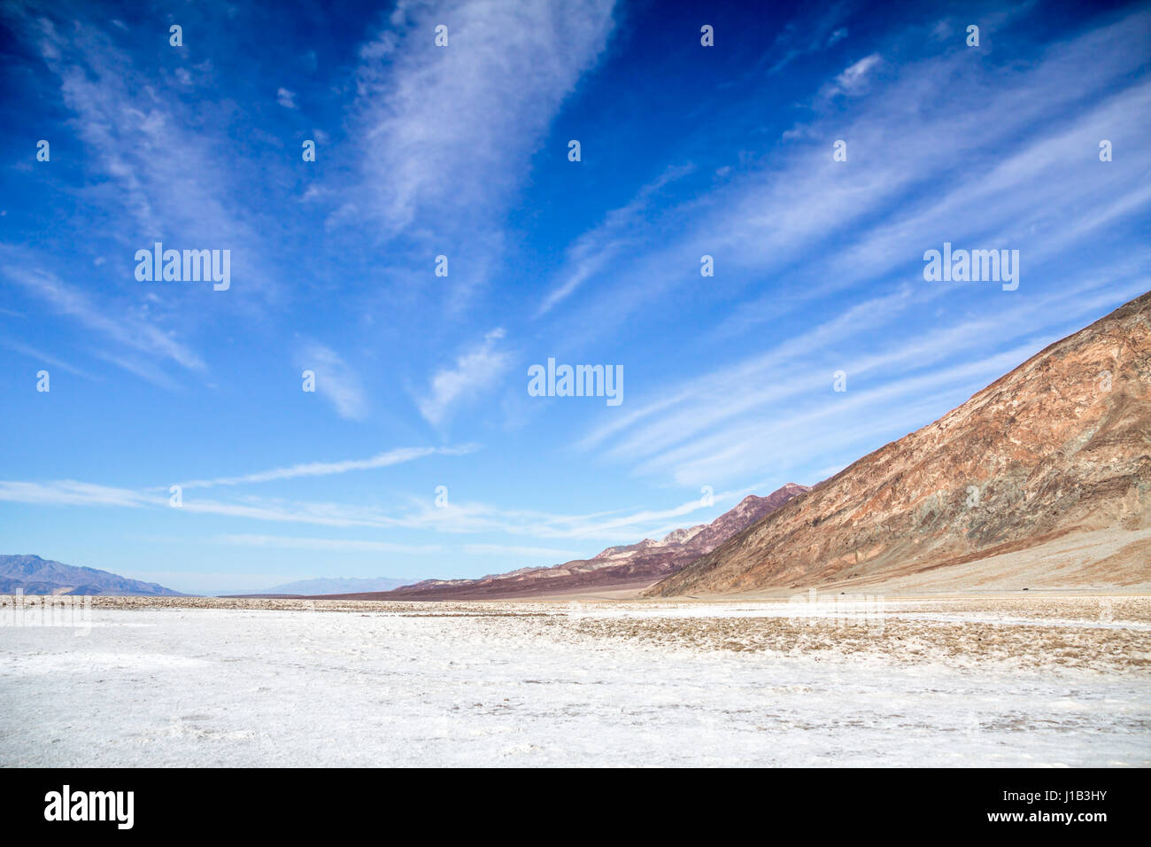 Saltflats of Badwater Basin, Death Valley National Park, CA.  Under a deep blue sky, radiating cirrus clouds lead - Stock Image
