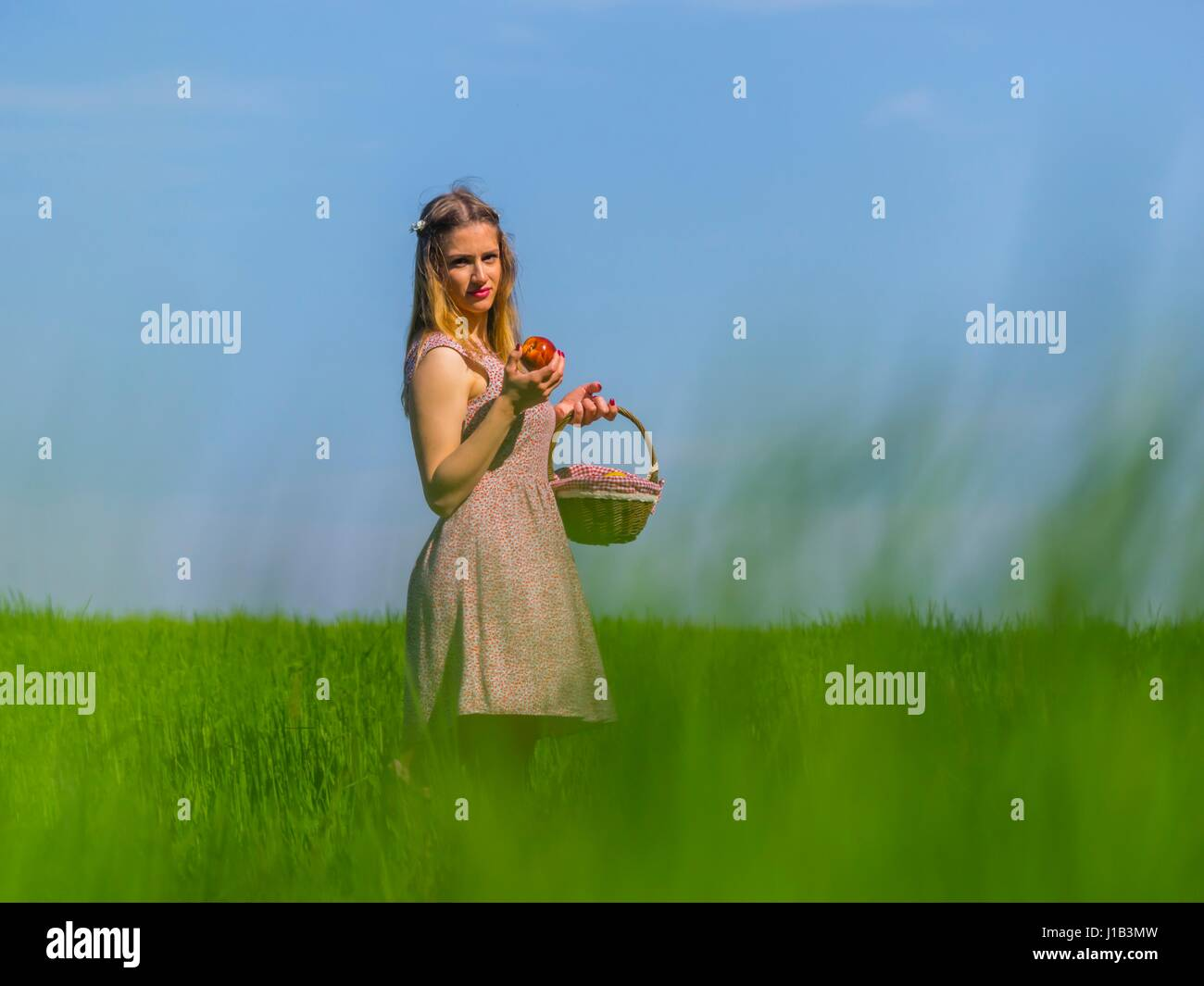 Country-girl apple and small basket in hand side-view three-quarter length eyes-contact looking at camera through - Stock Image