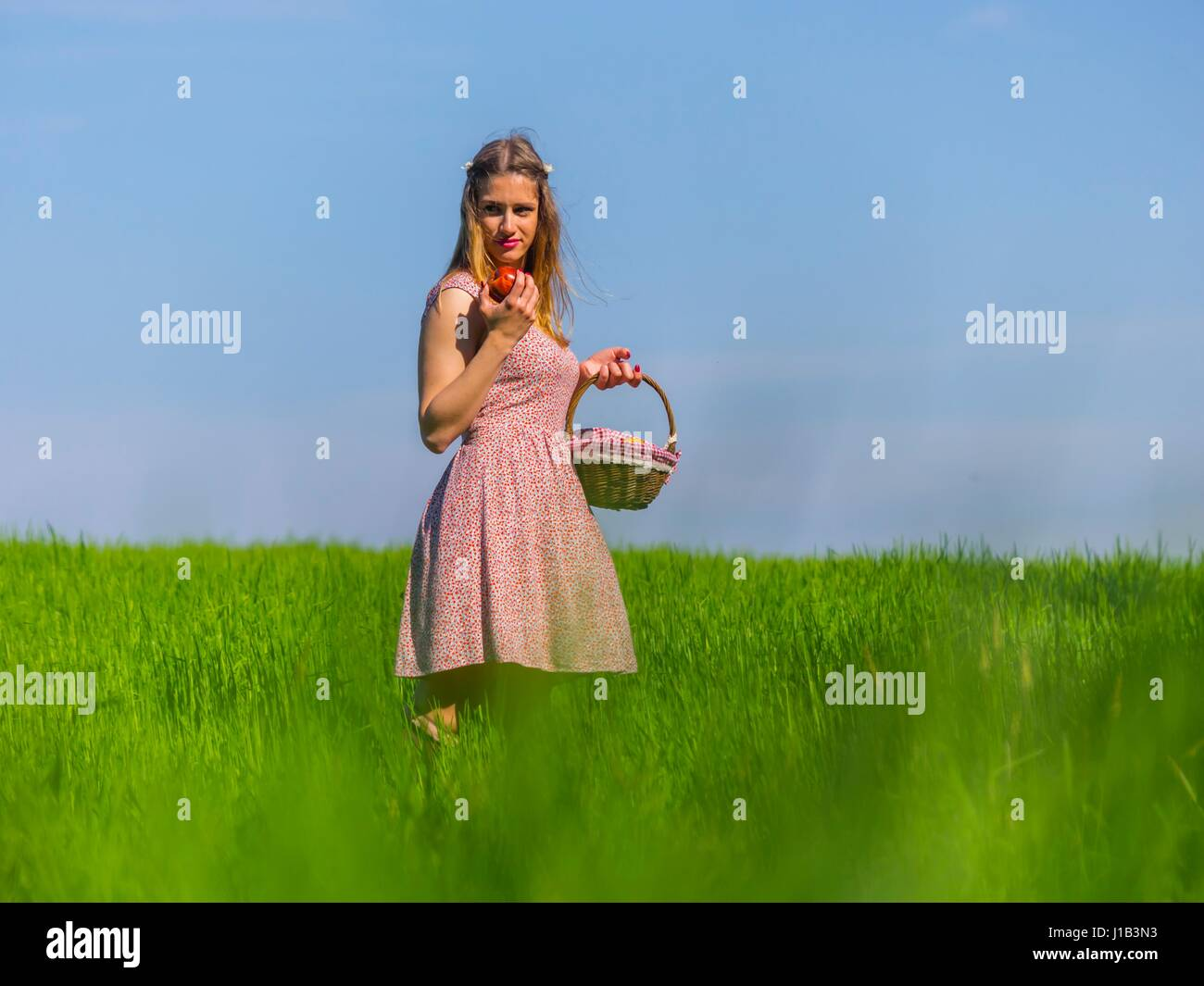 Country-girl apple and small basket in hand looking back serious hold, holding farm girl - Stock Image