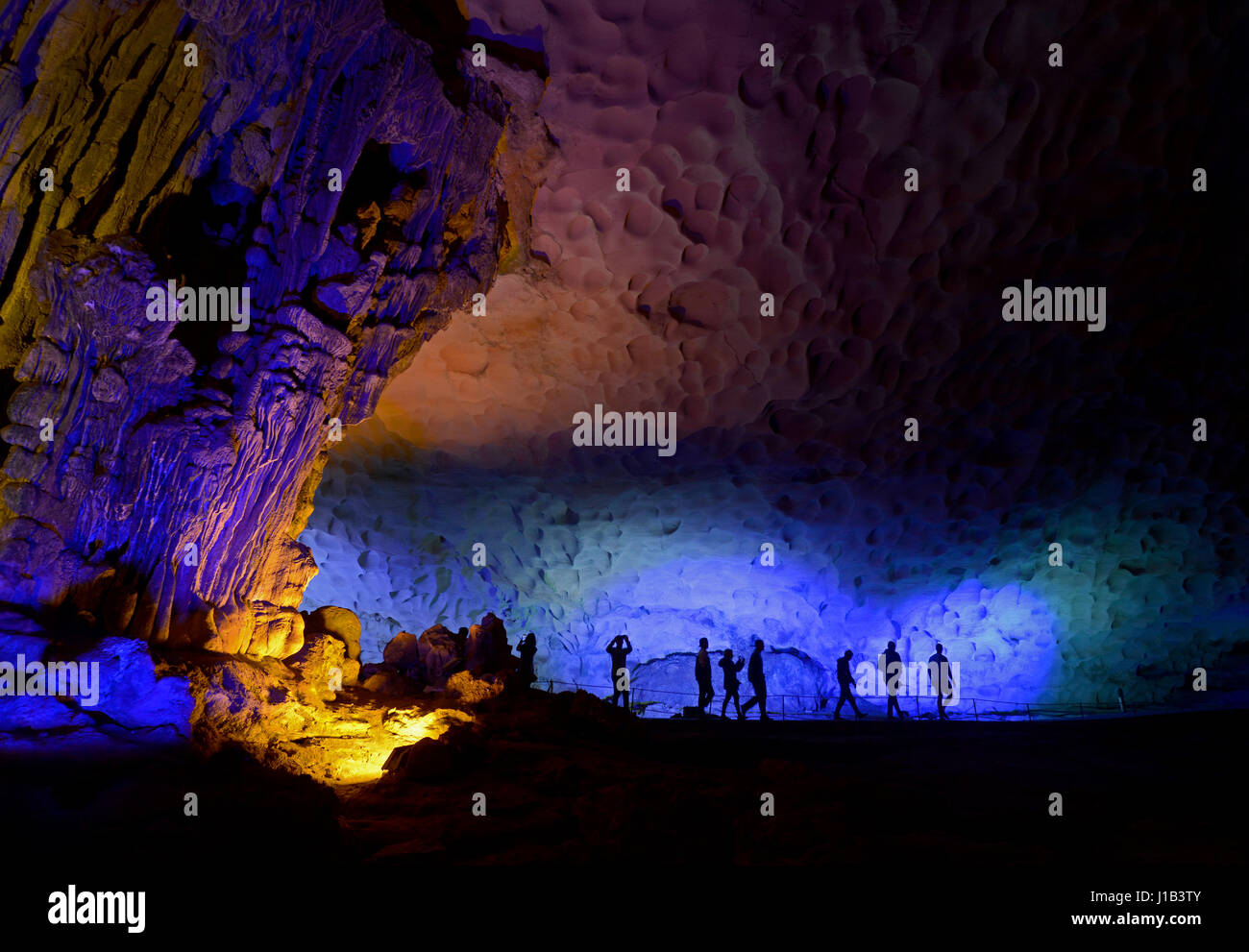 Silhouetted tourists visiting the the Sung Sot Caves (Amazing Cave) on Bo Hon Island in Halong Bay, Vietnam, which - Stock Image