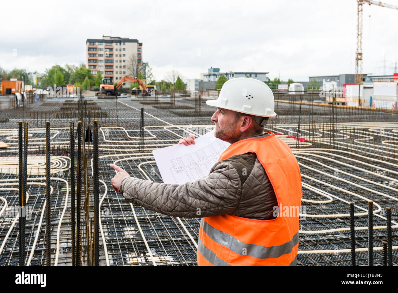 Construction supervisor with plan on site - Stock Image
