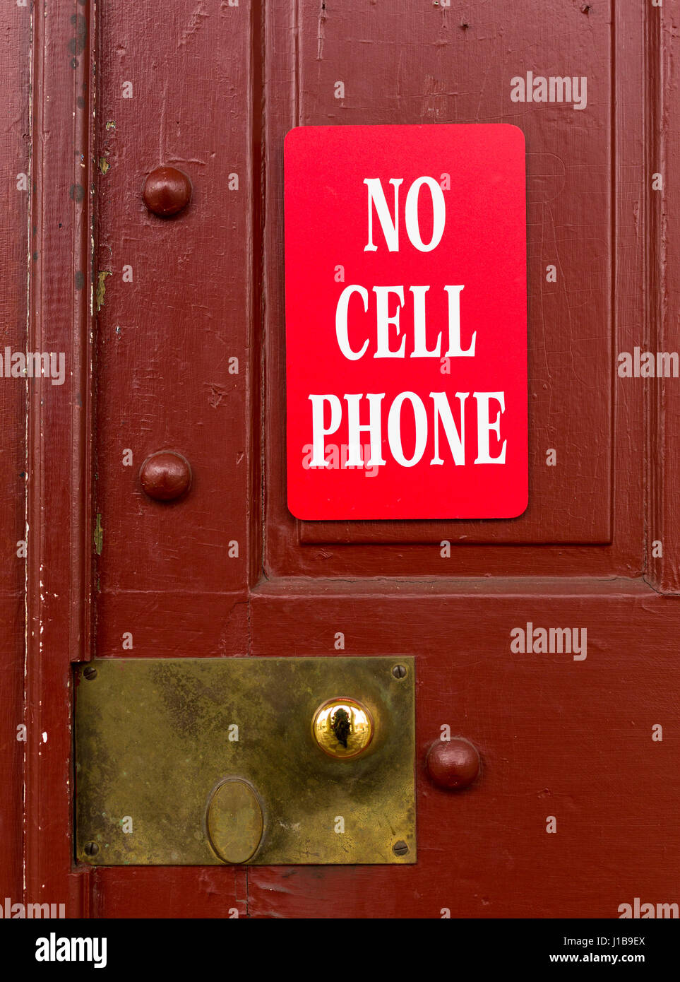 Sign on a door warning that no cell phone, smartphone or wireless phone usage is allowed - Stock Image
