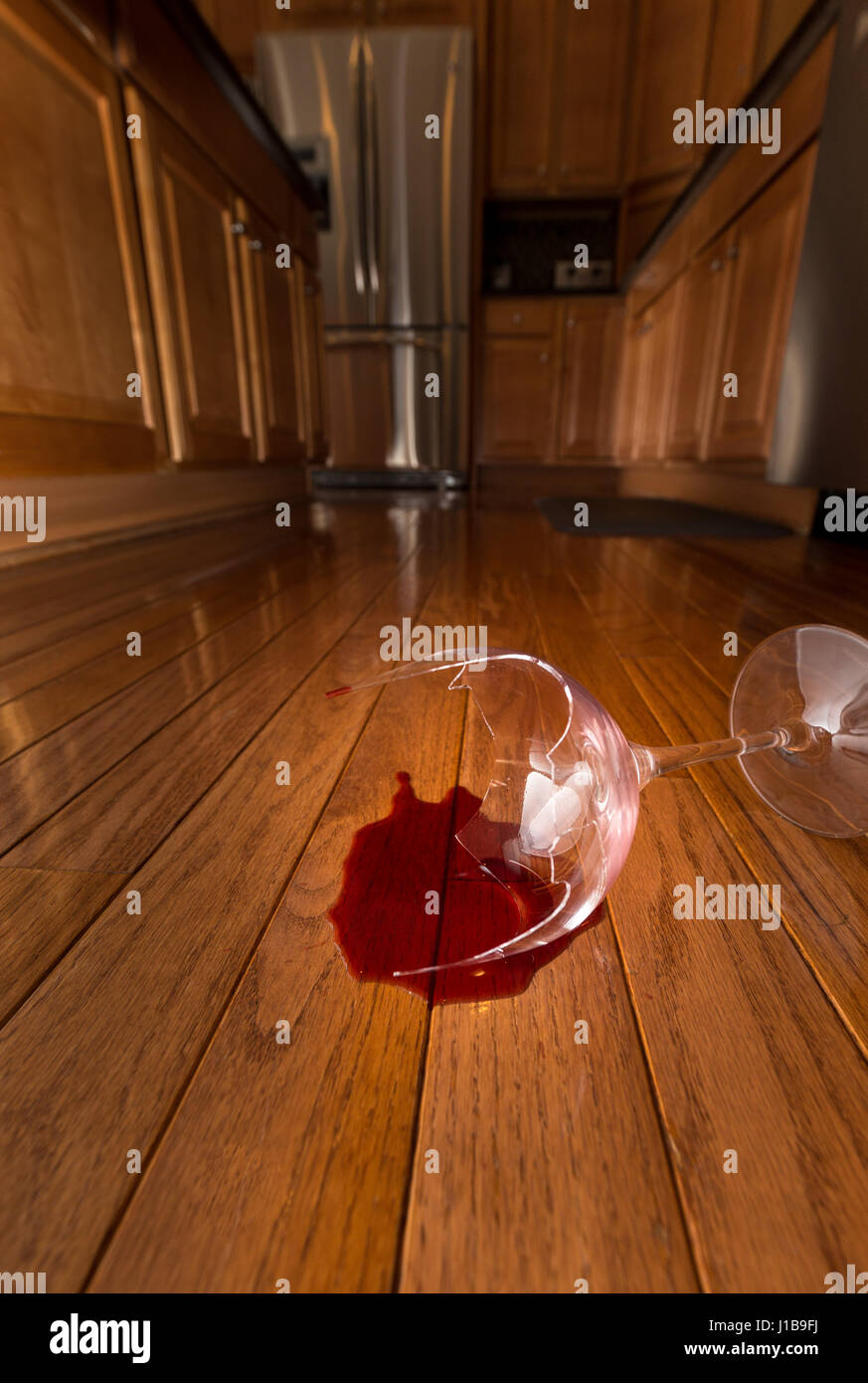 Broken wine glass on floor of modern kitchen - domestic violence concept - Stock Image