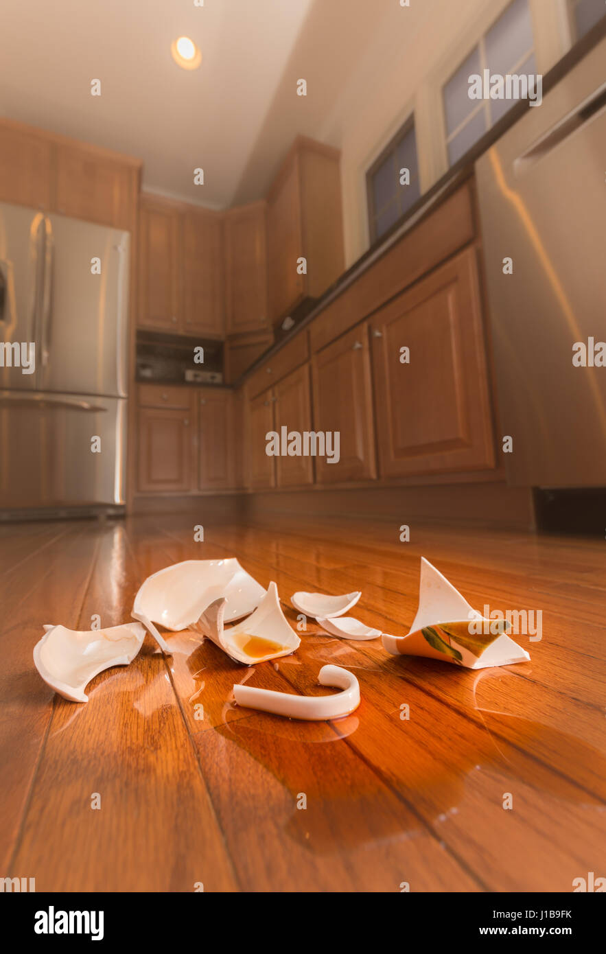 Broken coffee cup on floor of modern kitchen - domestic violence concept - Stock Image