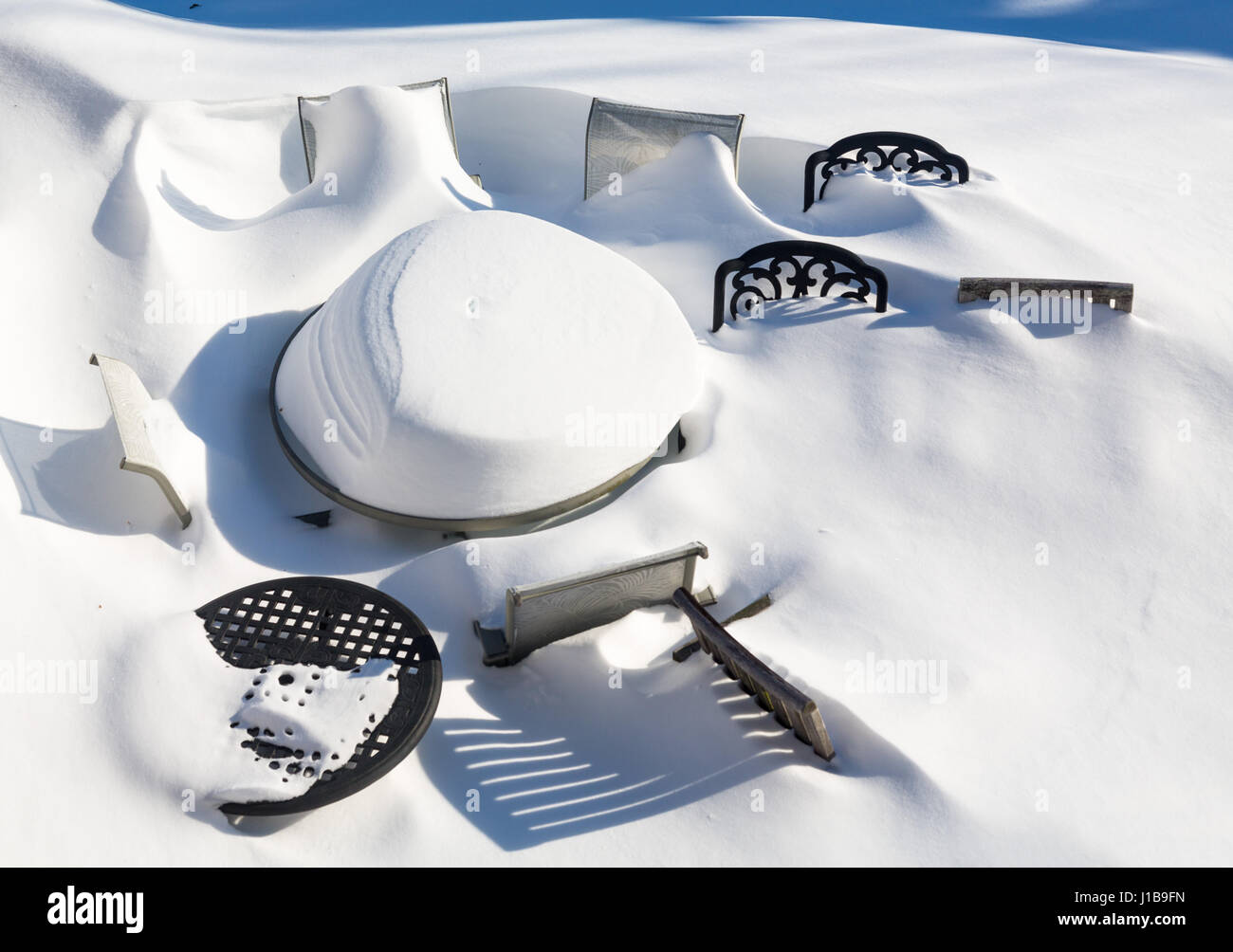 Outdoor garden furniture buried by snow in deep drift during a blizzard - Stock Image