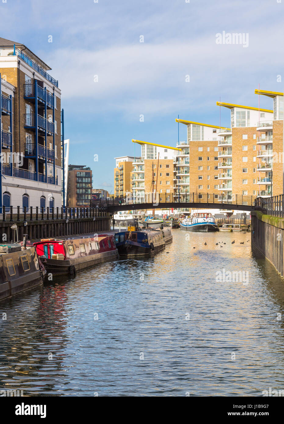 Limehouse Cut looking to the apartment buildings at Limehouse Basin Marina in Docklands with houseboats, London, - Stock Image