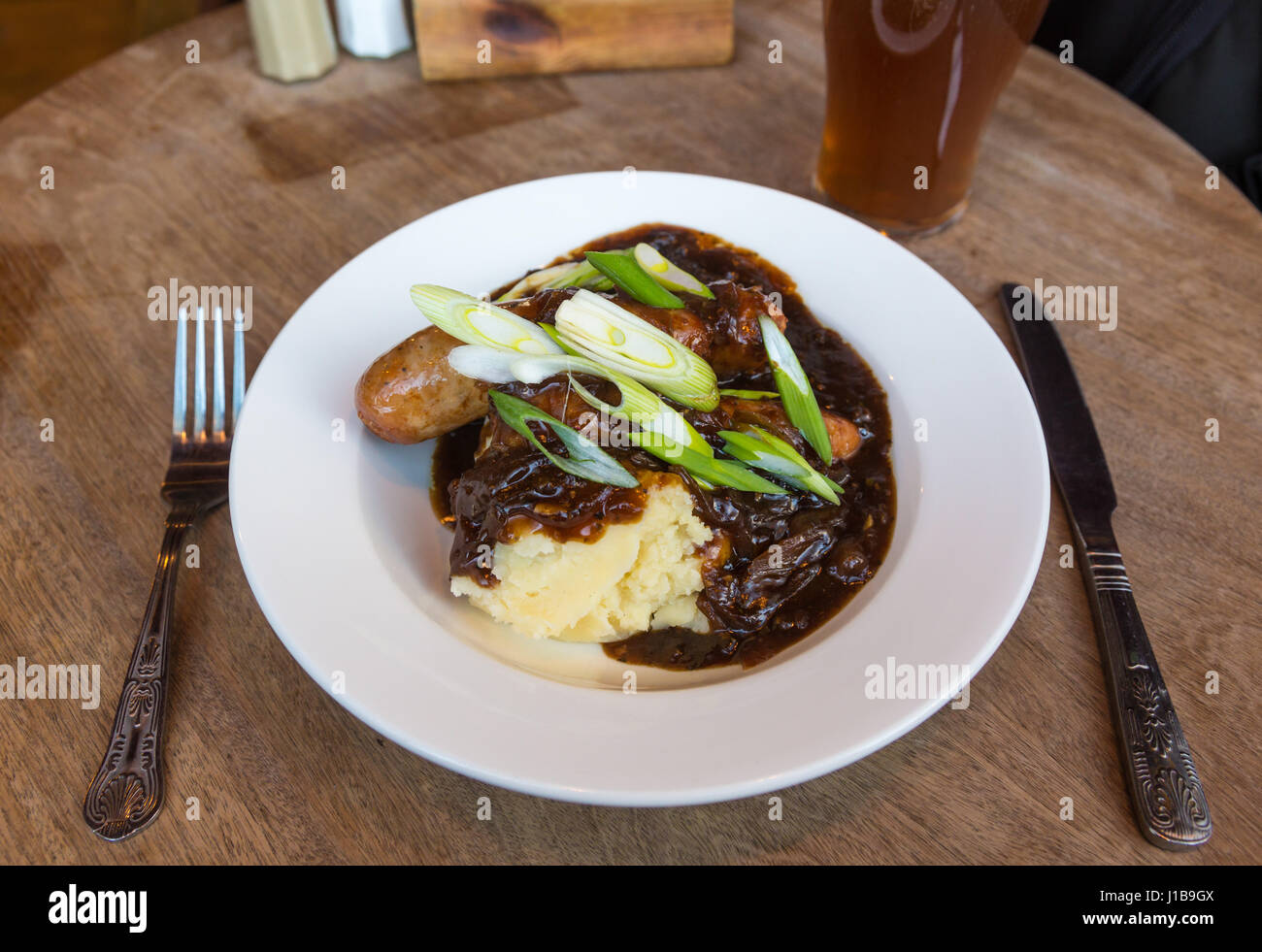Plate of traditional British pub food - plate of sausage and mash with onion gravy and a pint of real ale, UK - Stock Image