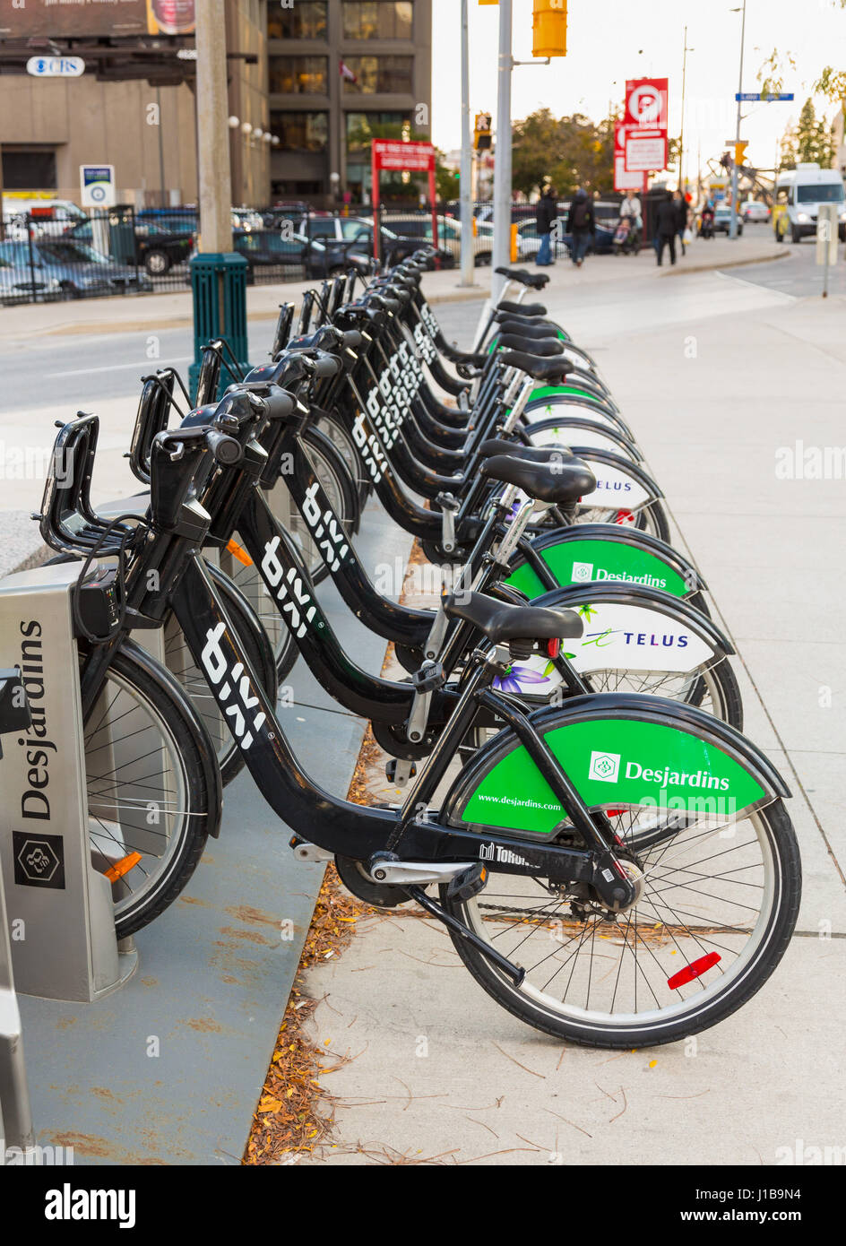Row of bike share cycle rental bicycles sponsored by Desjardins and Telus on the streets of Toronto in Ontario, - Stock Image